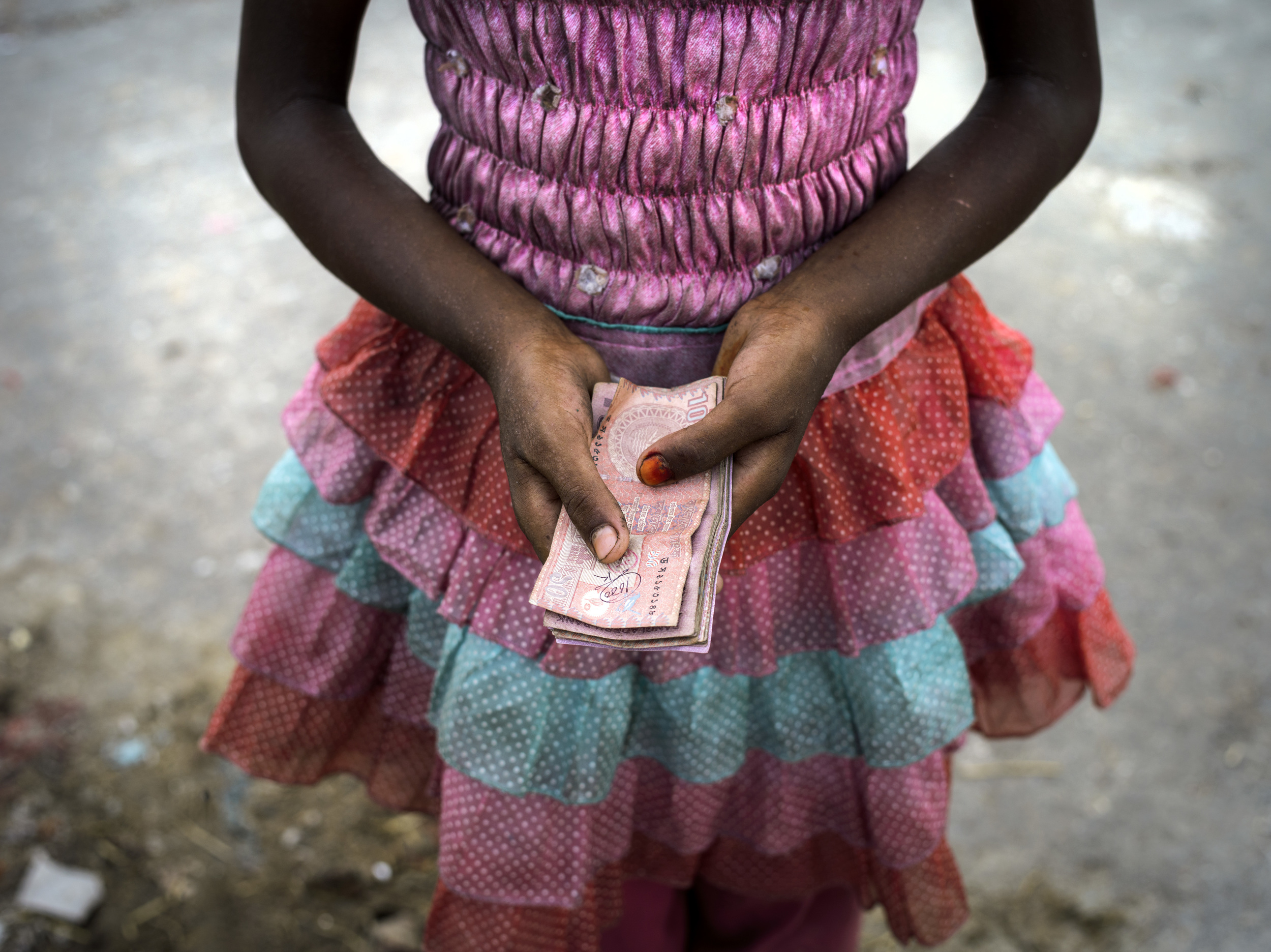 A girl shows the money her family made that day at Aminbazar Sanitary Landfill, Dhaka.