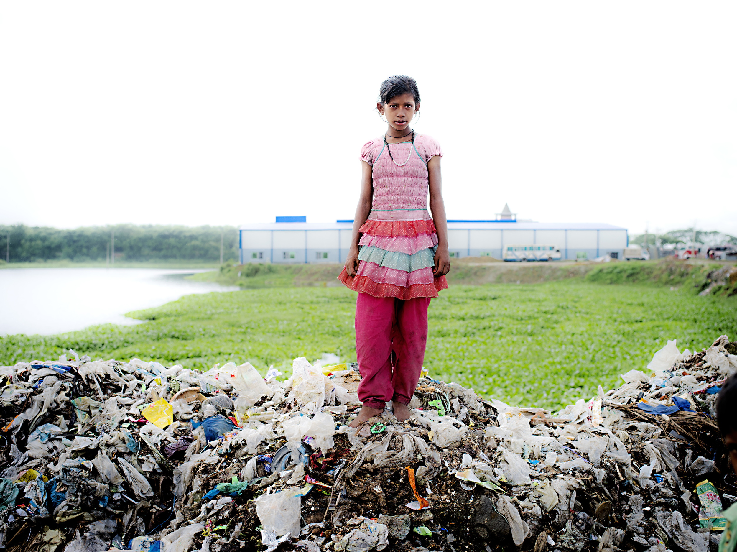 A girl confidently stands atop an area of Aminbazar Sanitary Landfill.