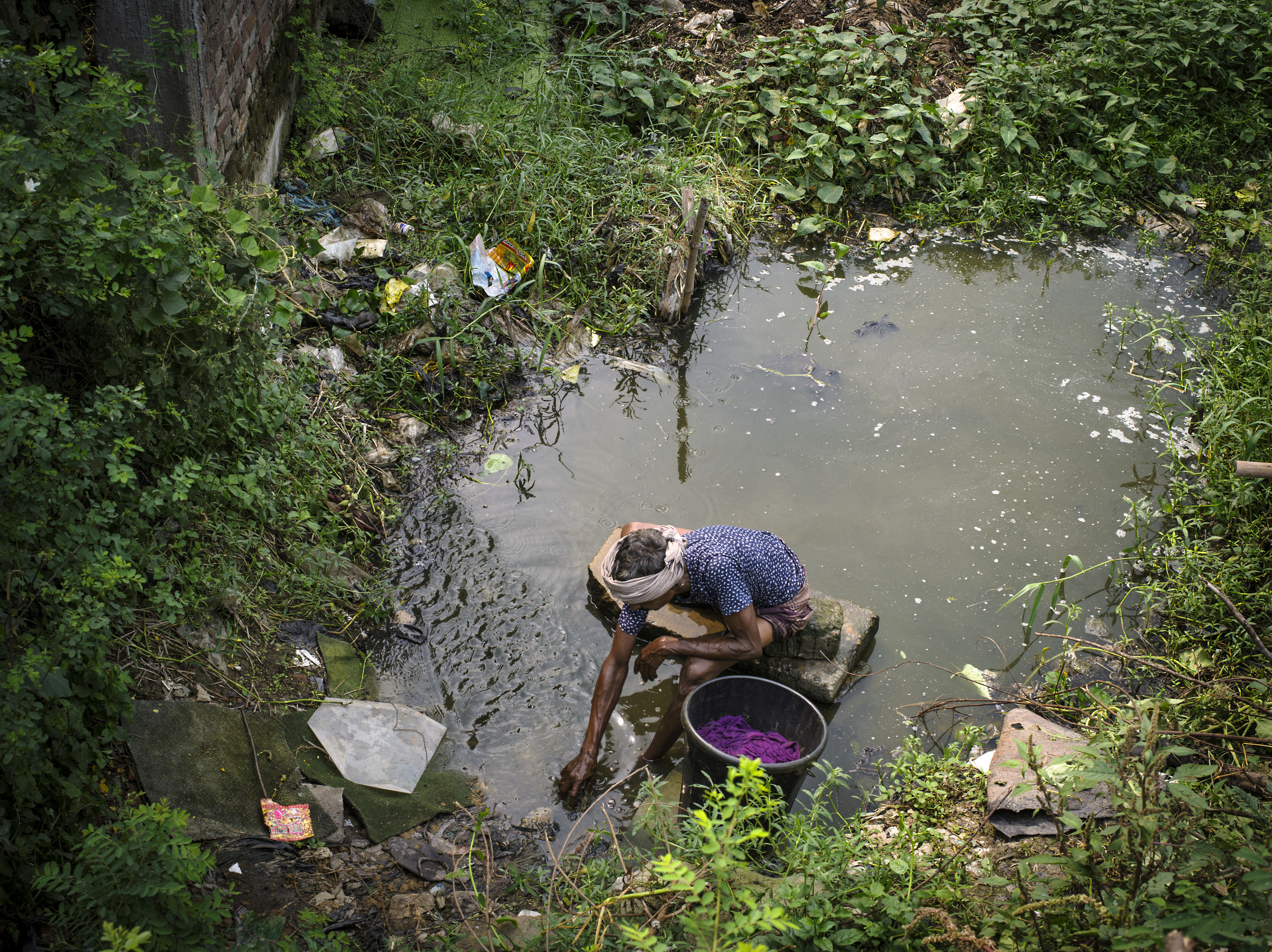 Man washing plastics in water. Mutual Landfill, Dhaka.