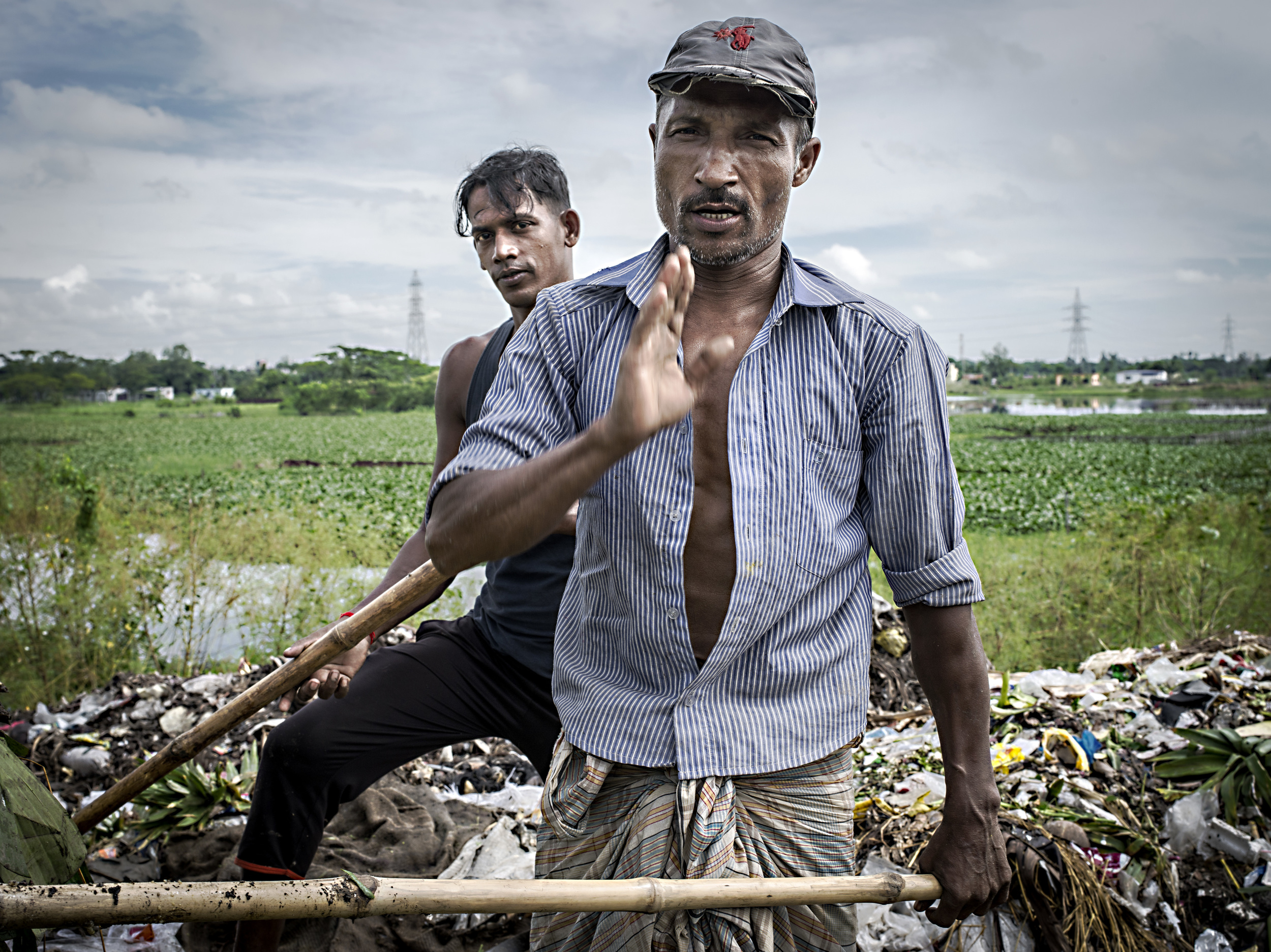 Men explaining how they sort trash at Narayanganj waste dump area.