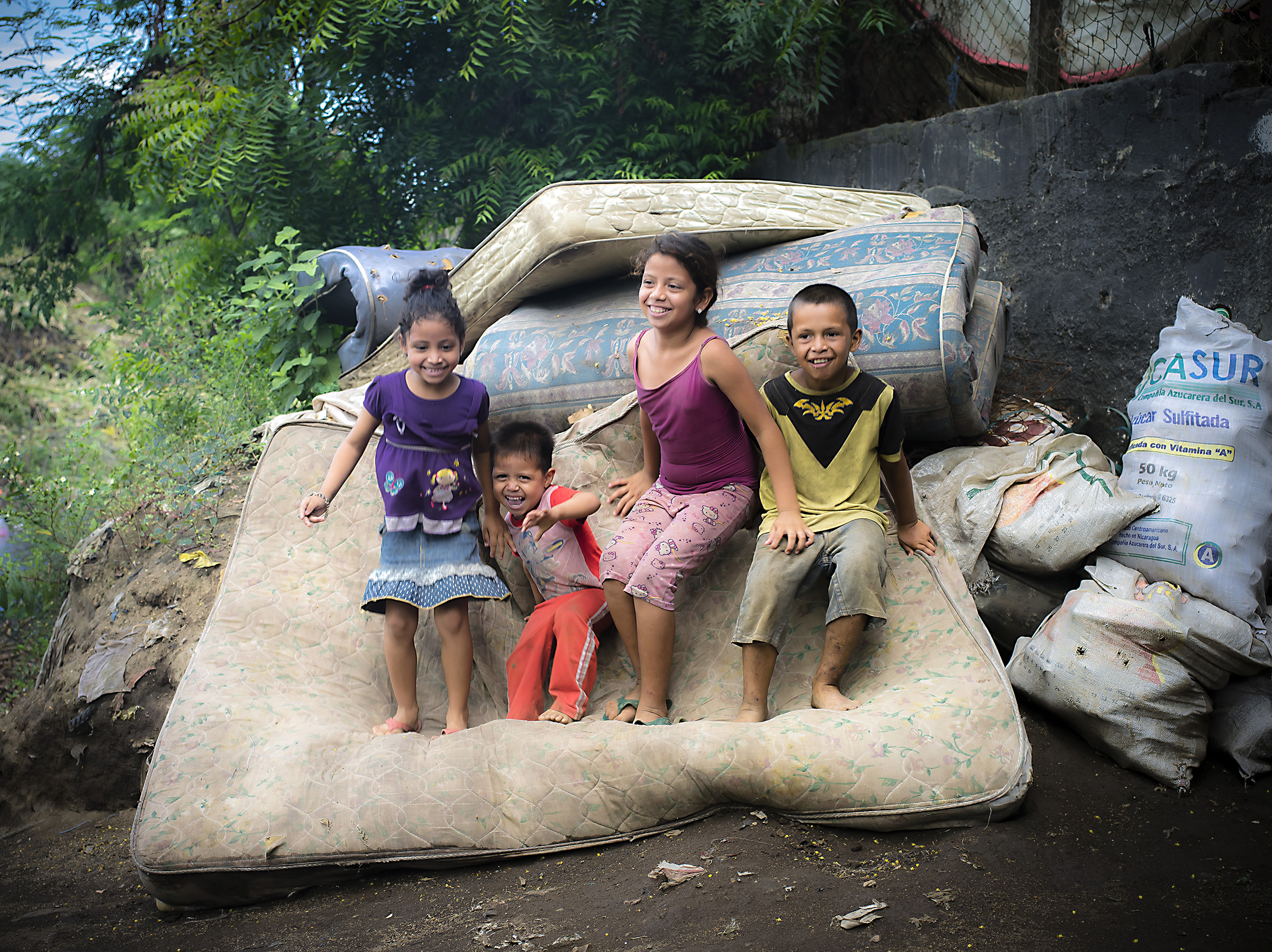 Fernanda, Norlan, Siara, and Pedro bouncing on mattresses found in the dump site. Mattresses like these can be reused as a mattress or the coils inside will be used to make a fence.