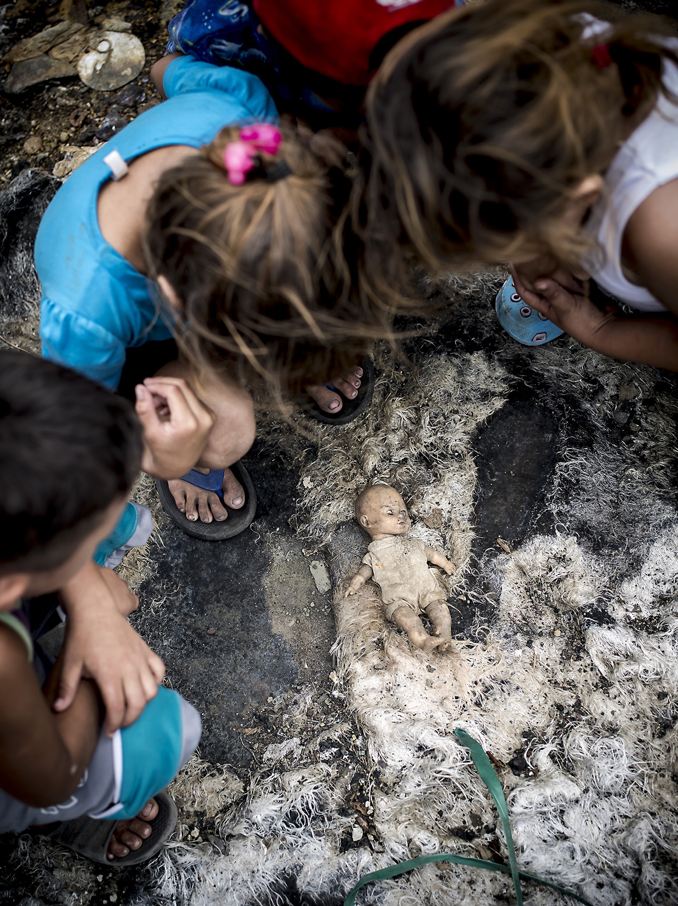 Kids finding a doll on top of animal skin.