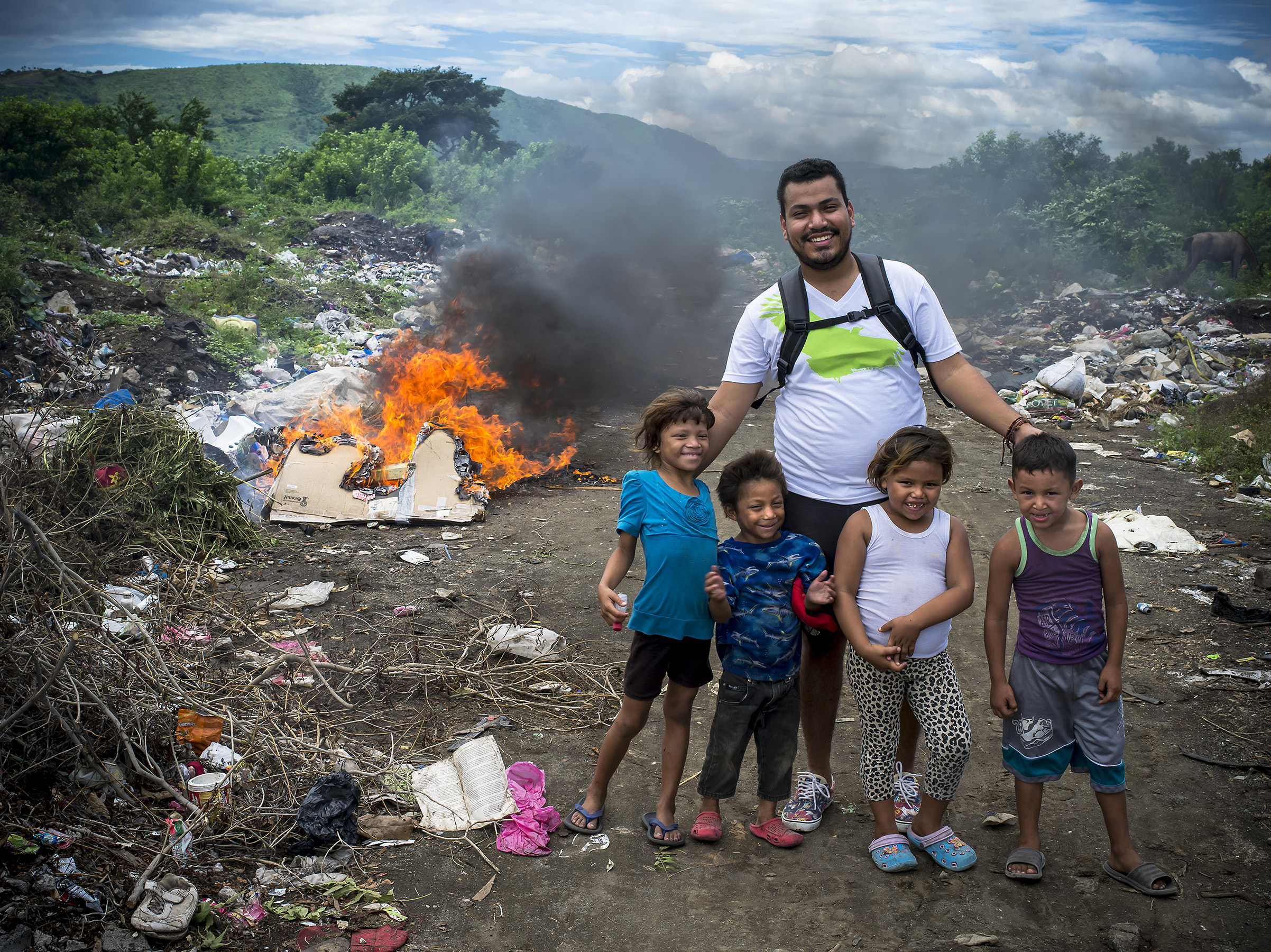 Program Supervisor, Engelbert Blanco, with the kids outside their home were trash is thrown and burned.