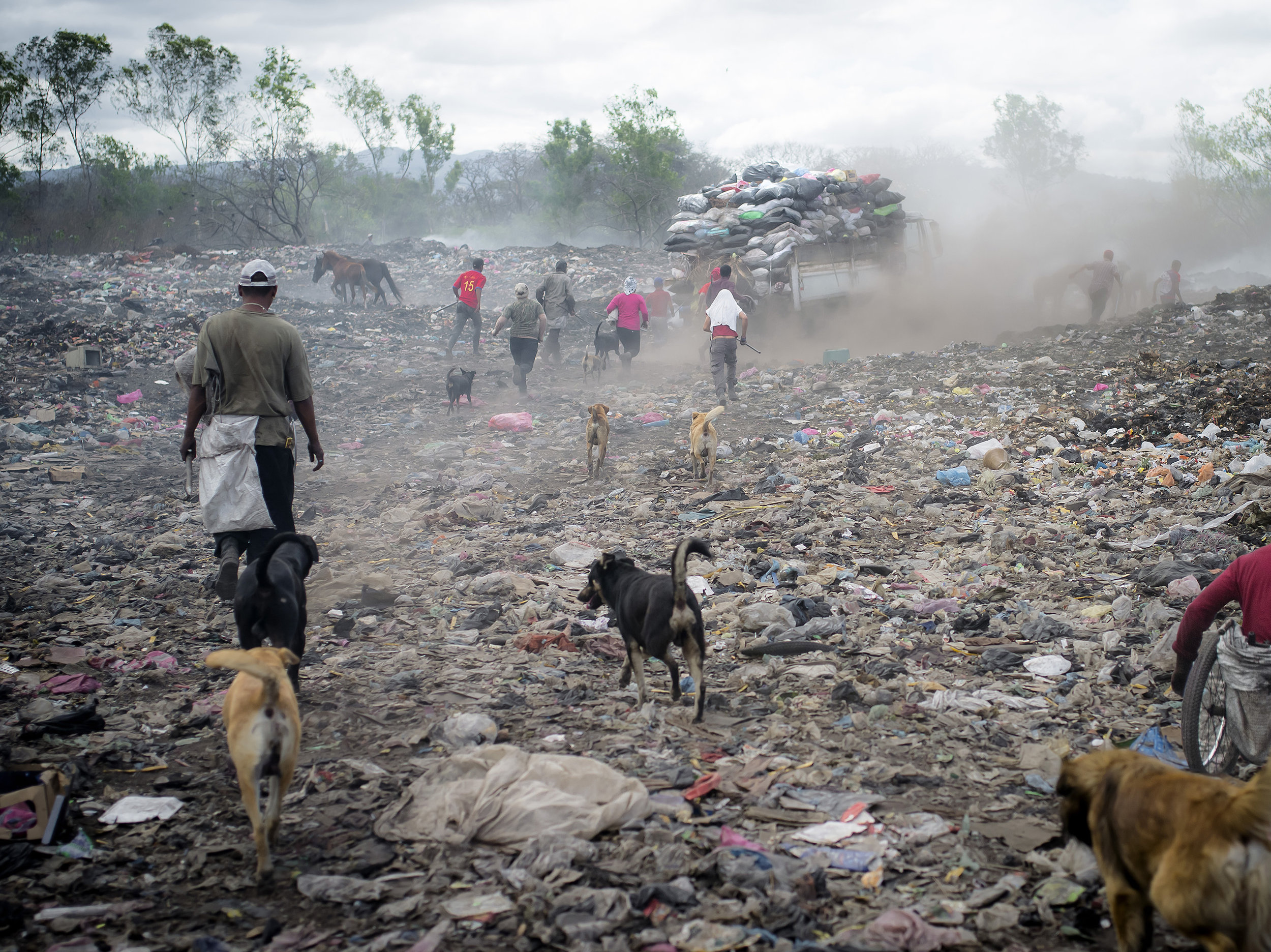 Families run towards a dump truck to have a fair pick of the materials they are searching for, including a elderly man in a wheelchair.