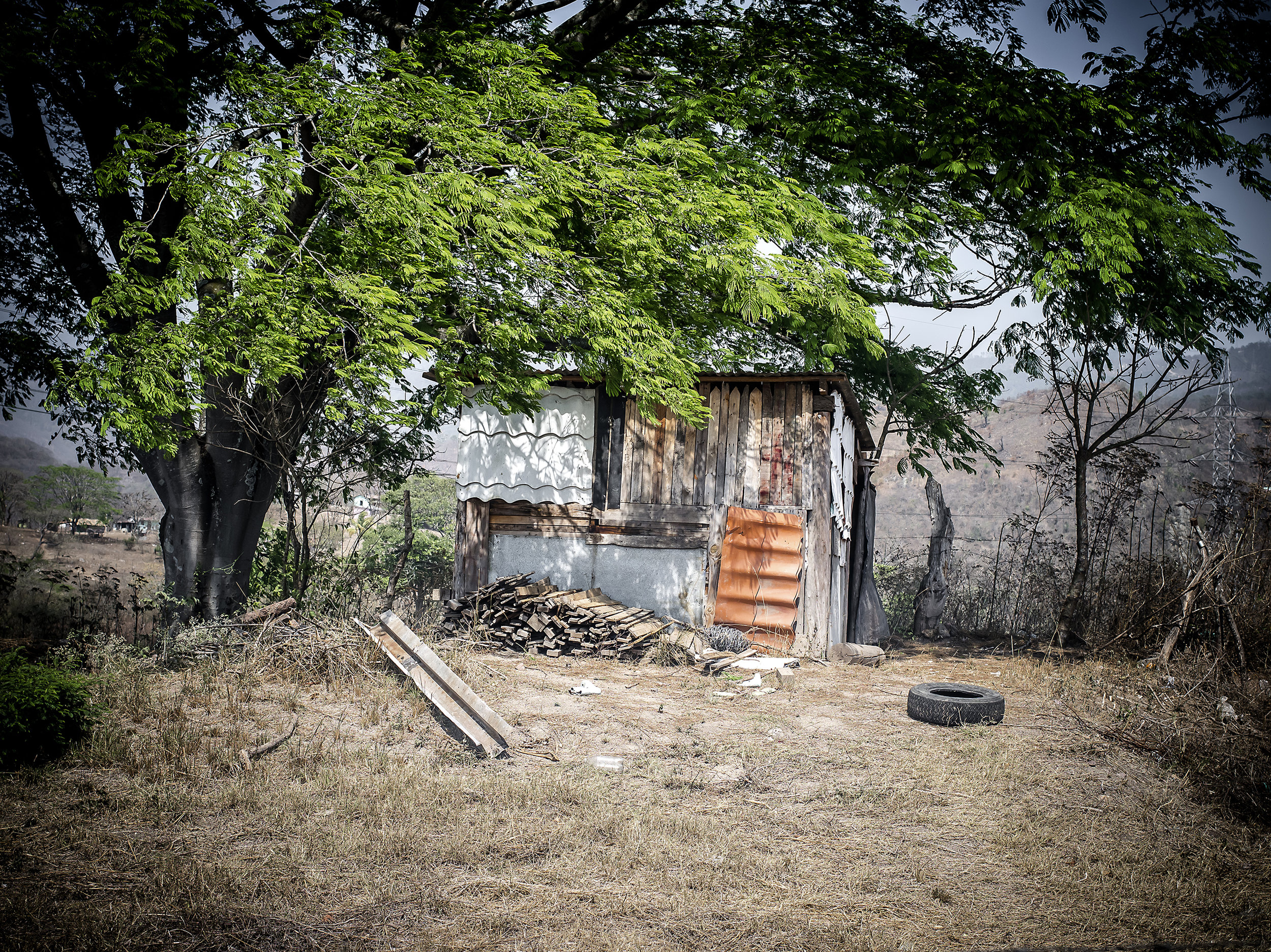 Many informal recyclers live in houses made of dump materials and wood. They do not have water or electricity. It is in a large plain with direct sun. This house luckily has shade from a tree.