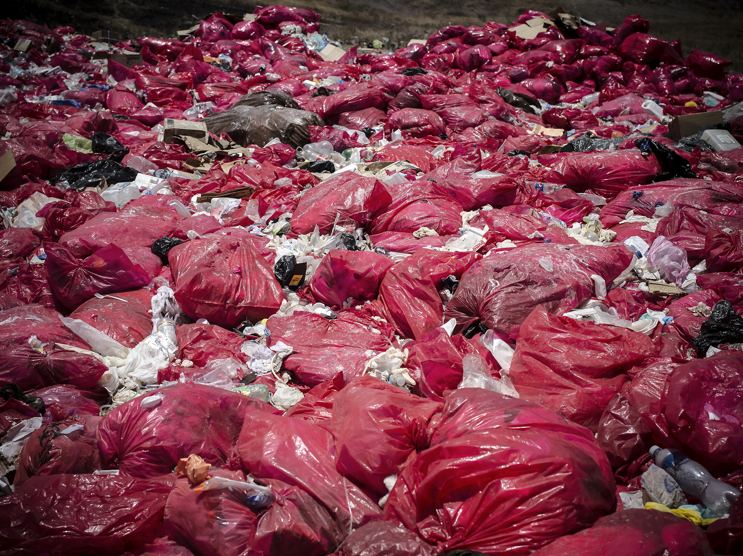 Thousands of hazardous medical waste bags pile on top of each other.