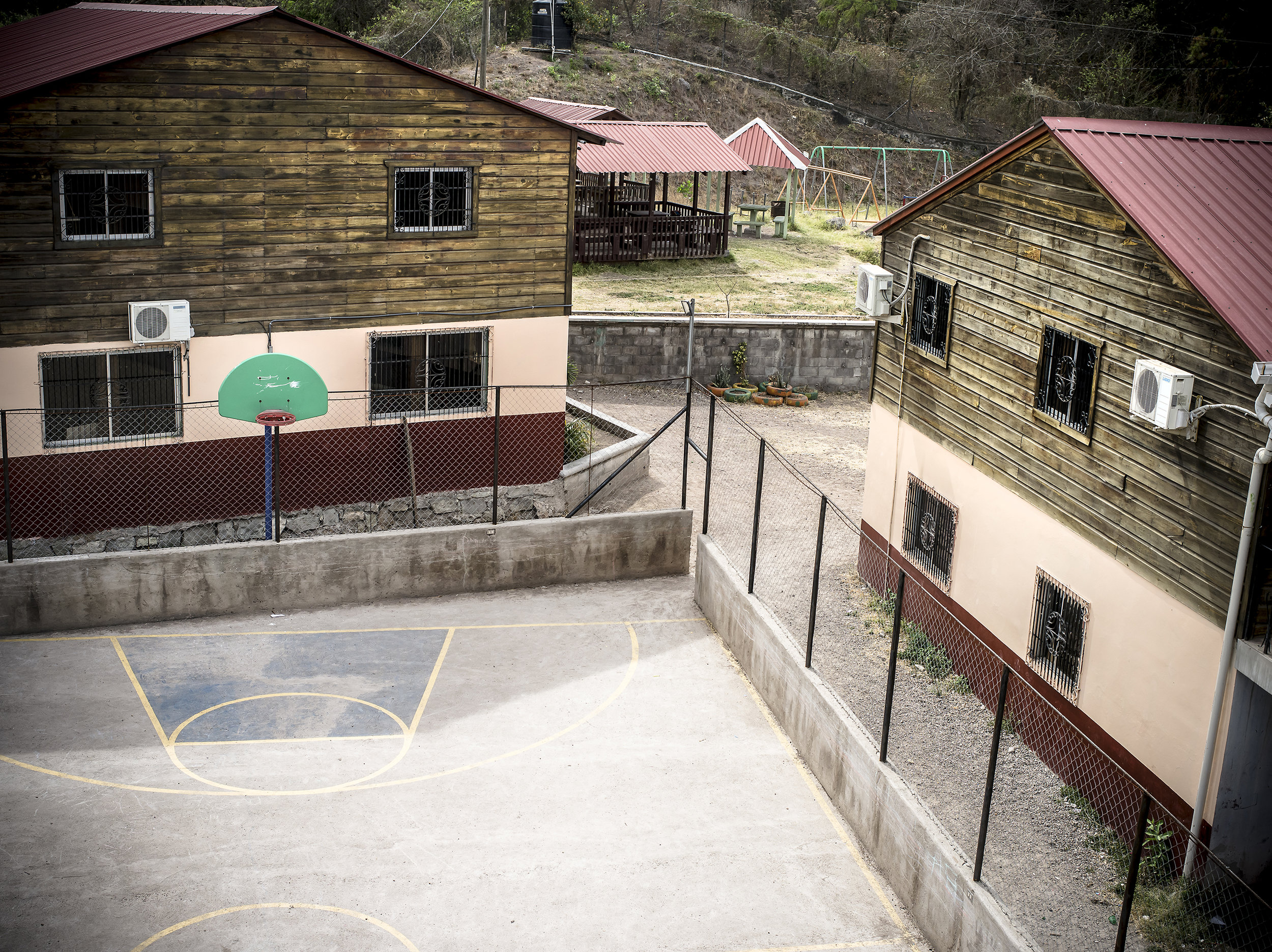 AFE have many buildings here you can see two school buildings with a basketball court.