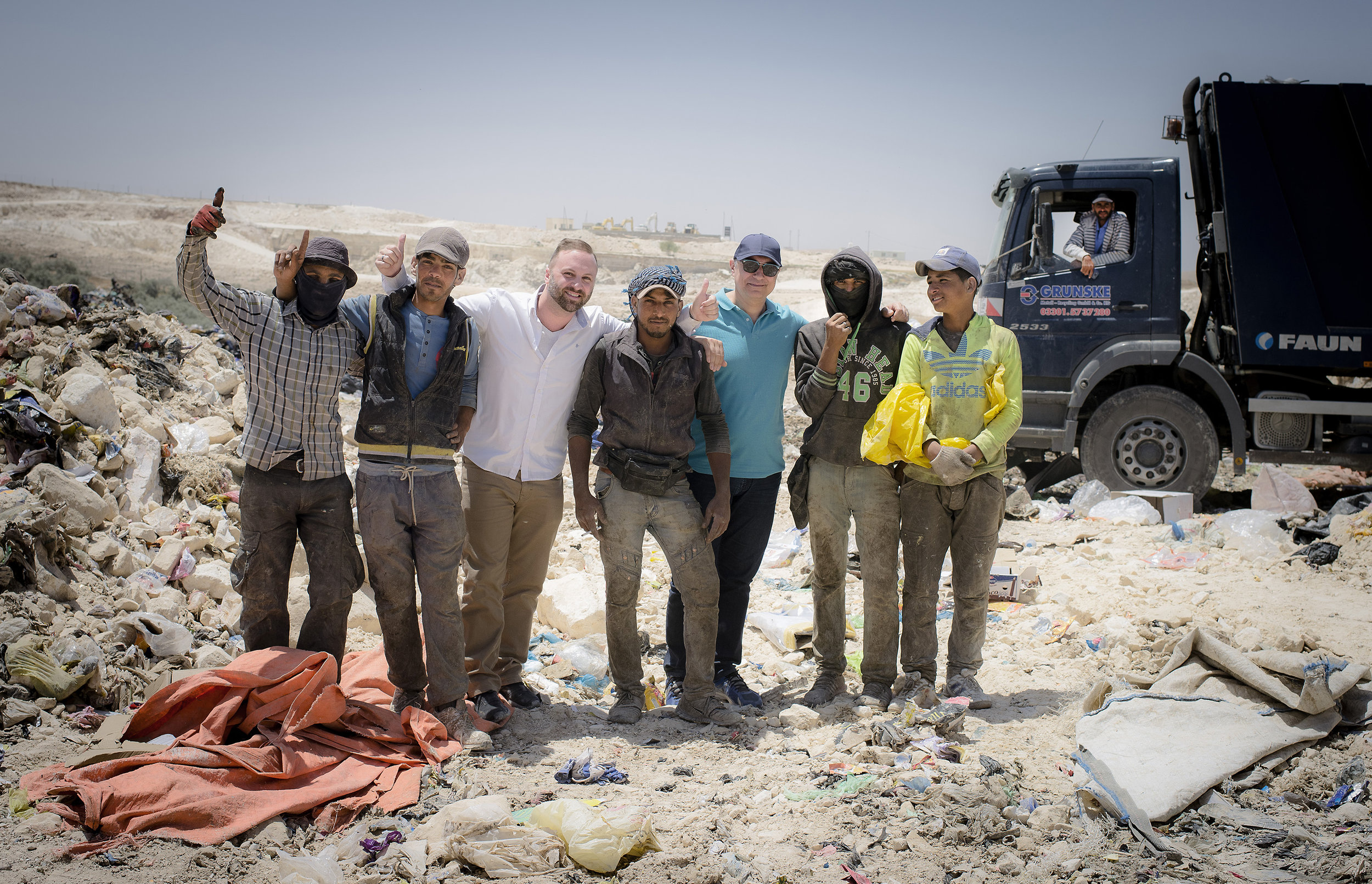 Timothy Bouldry and Antonis Mavropoulos pose with Syrians at the Al Ekaider dumpsite in Irbid, Jordan.