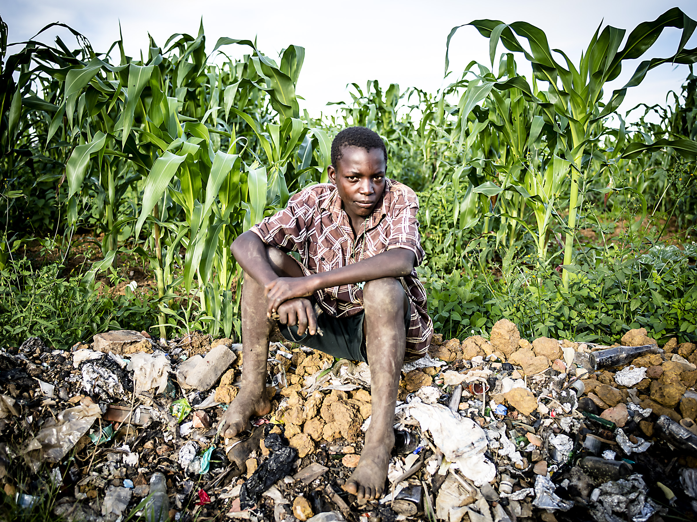 A boy from the informal dumpsite high on a hill in Masaka where they also grow corn. Mbarara