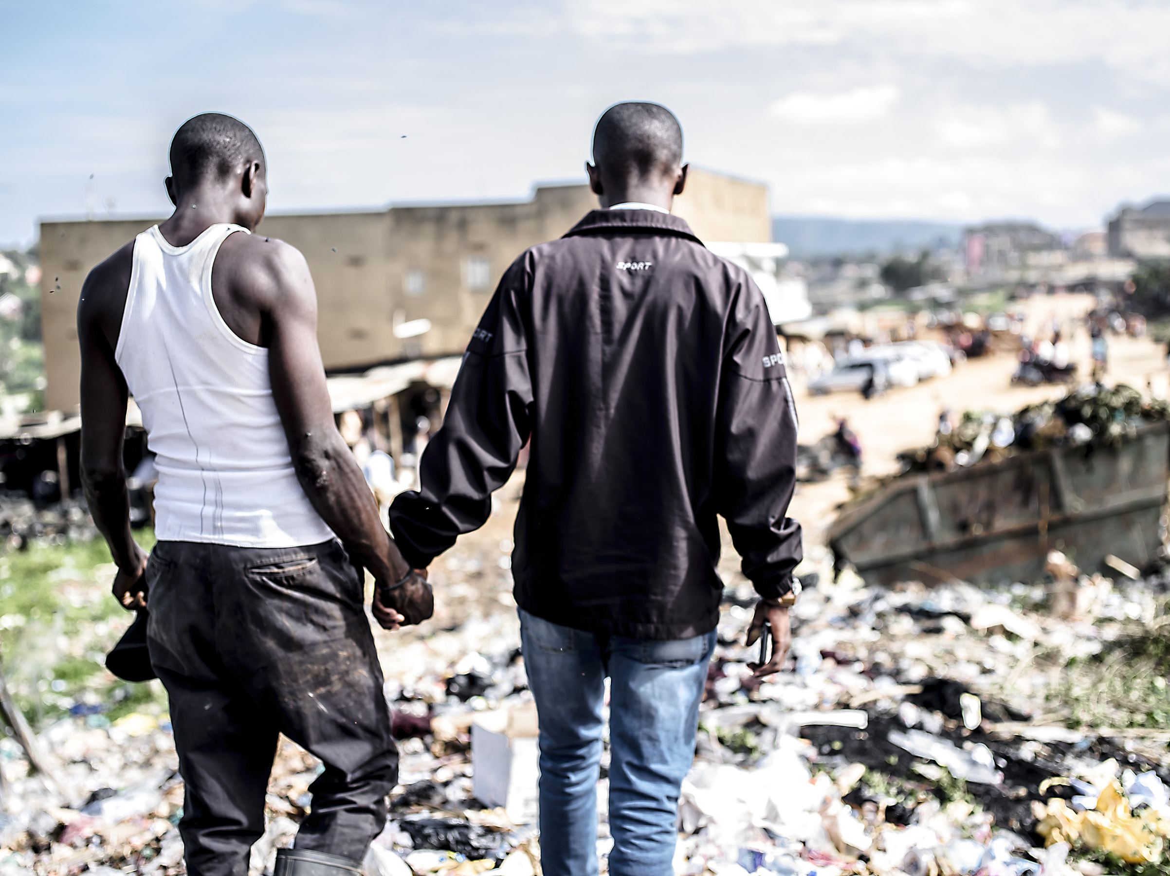 Taremwa Sam Rwabwehare holds hands with an informal recycler as they lead one another through the trash to talk about the worker's life, his work and the area. Mbarara.