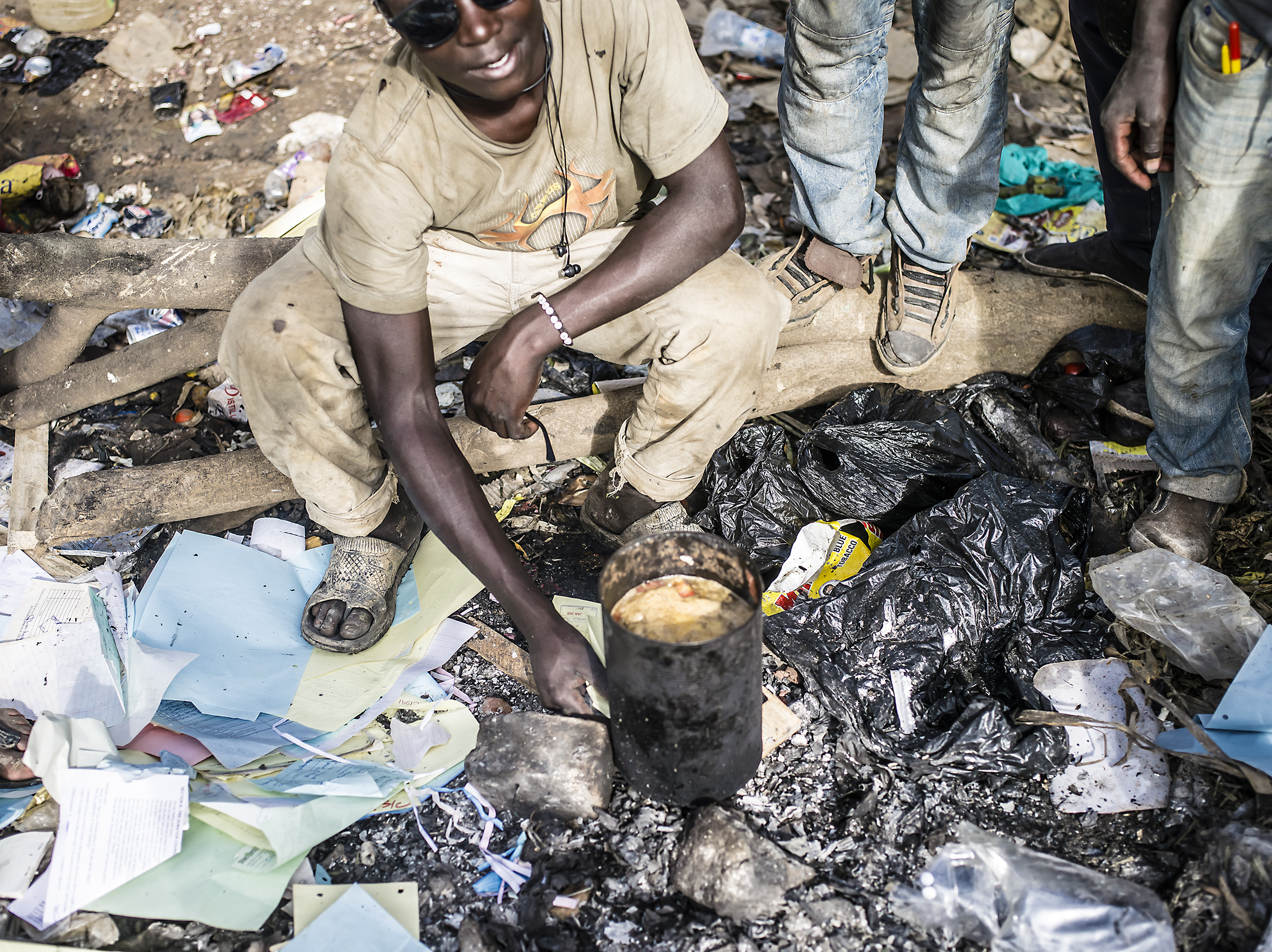 A young man cooks soup in the trash from himself and his friends. Mbarara.