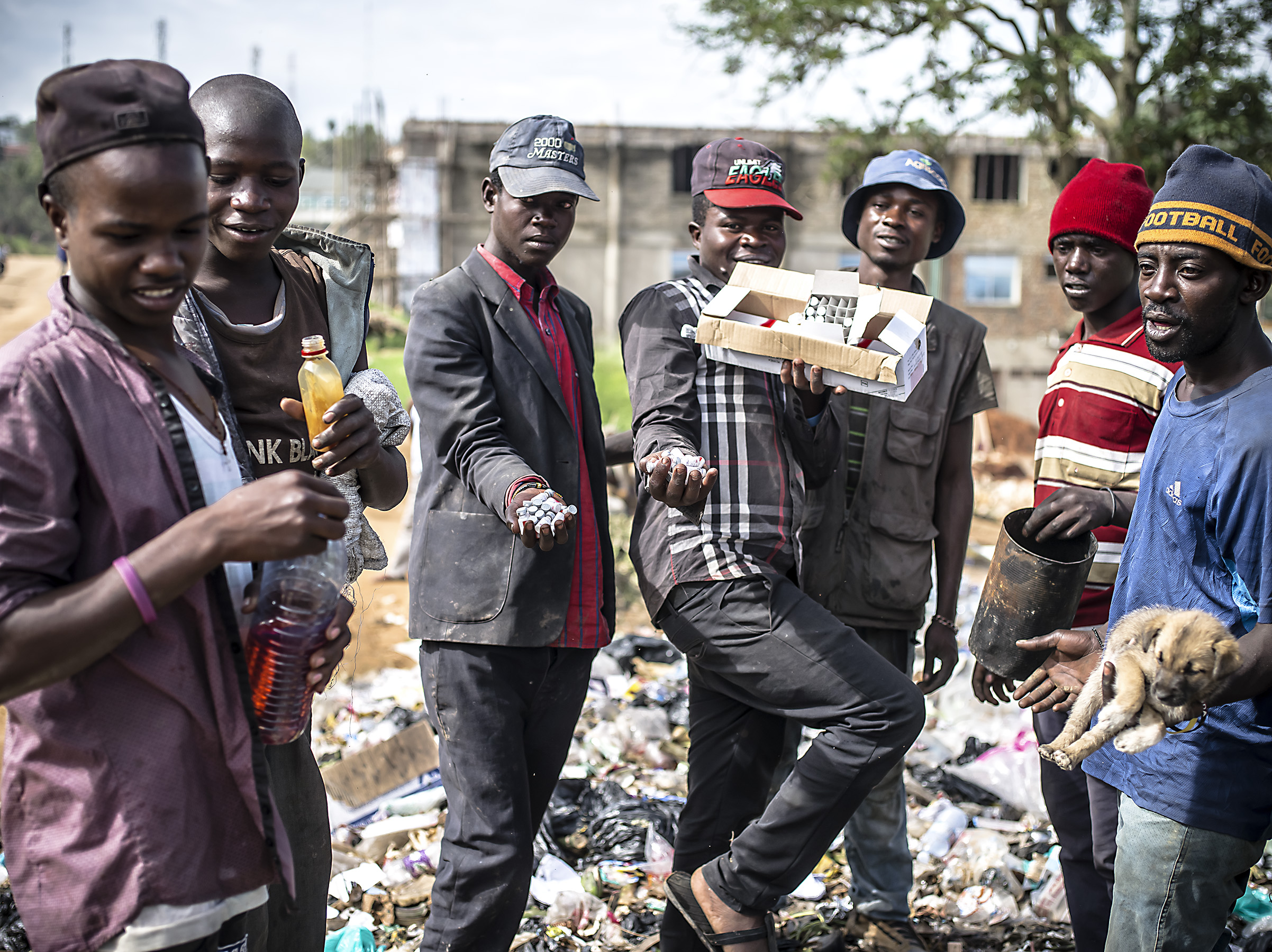 A group of men show me various things they have with them from the trash area including, glue for huffing, medicine waste they may reuse, a can they cook food from and a puppy. Mbarara.