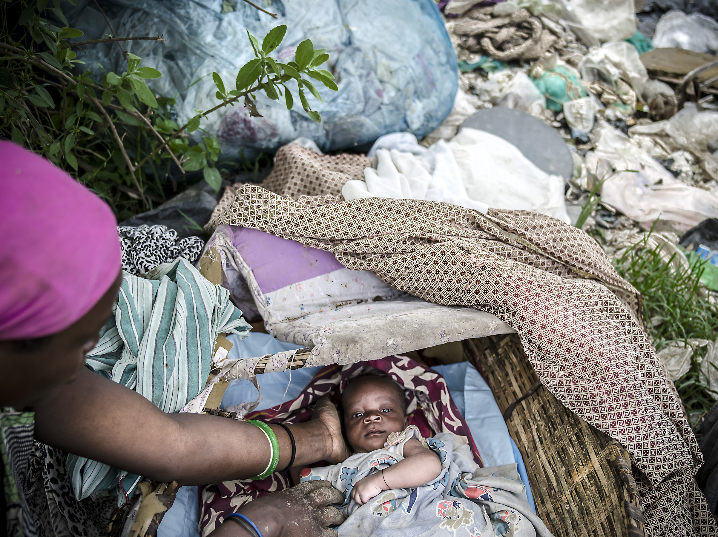 A woman puts her baby to rest after breast feeding in Masaka dumpsite.