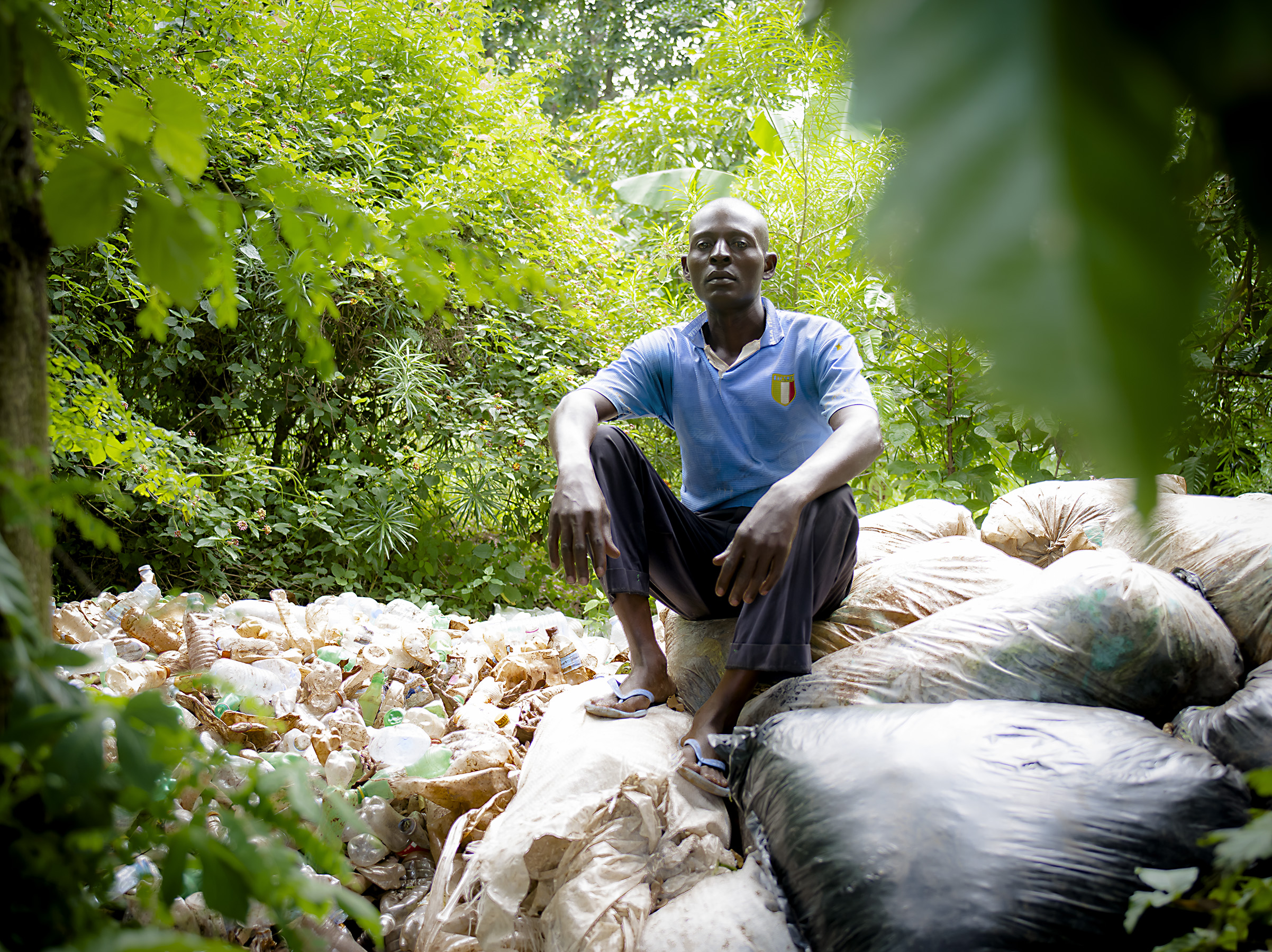 A man sita on bottles collected from the Njeru dumpsite.