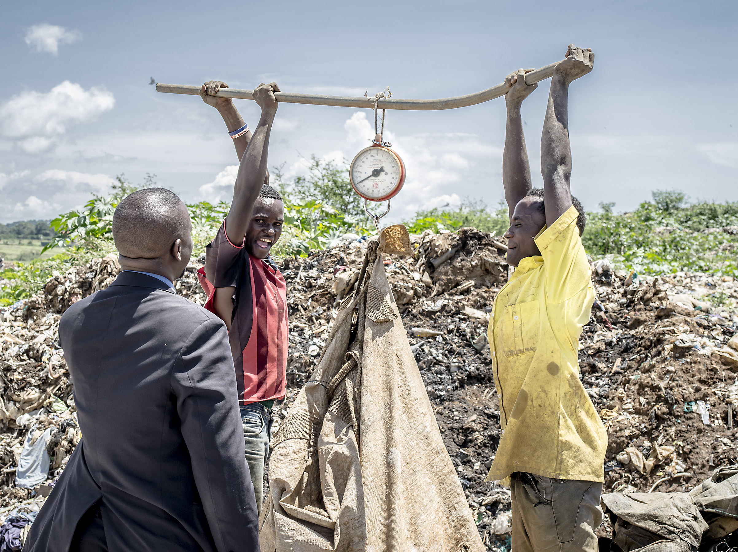 Men weigh materials they collected from the trash next to a person visiting from the environmental offices of Kampala.