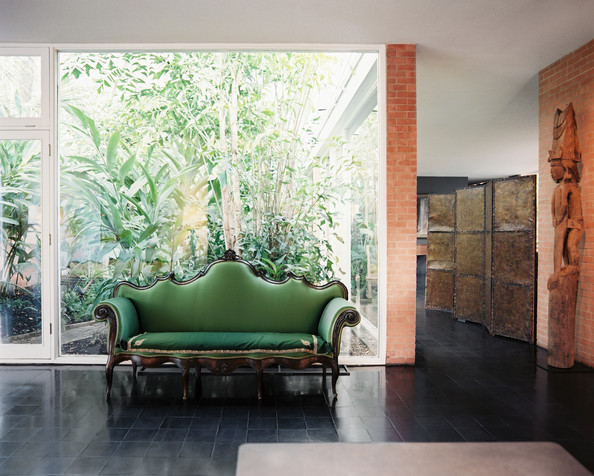 A green sofa in front of a wall of windows (Source: Lonny)