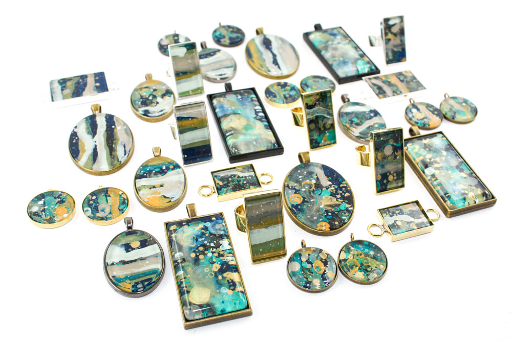 """These jewelry pieces are acrylic and glass that I splatter painted on the backside - I made these a few days after Day 16's challenge (the """"seriDRIPitous"""" pendants). This new series will launch soon!"""