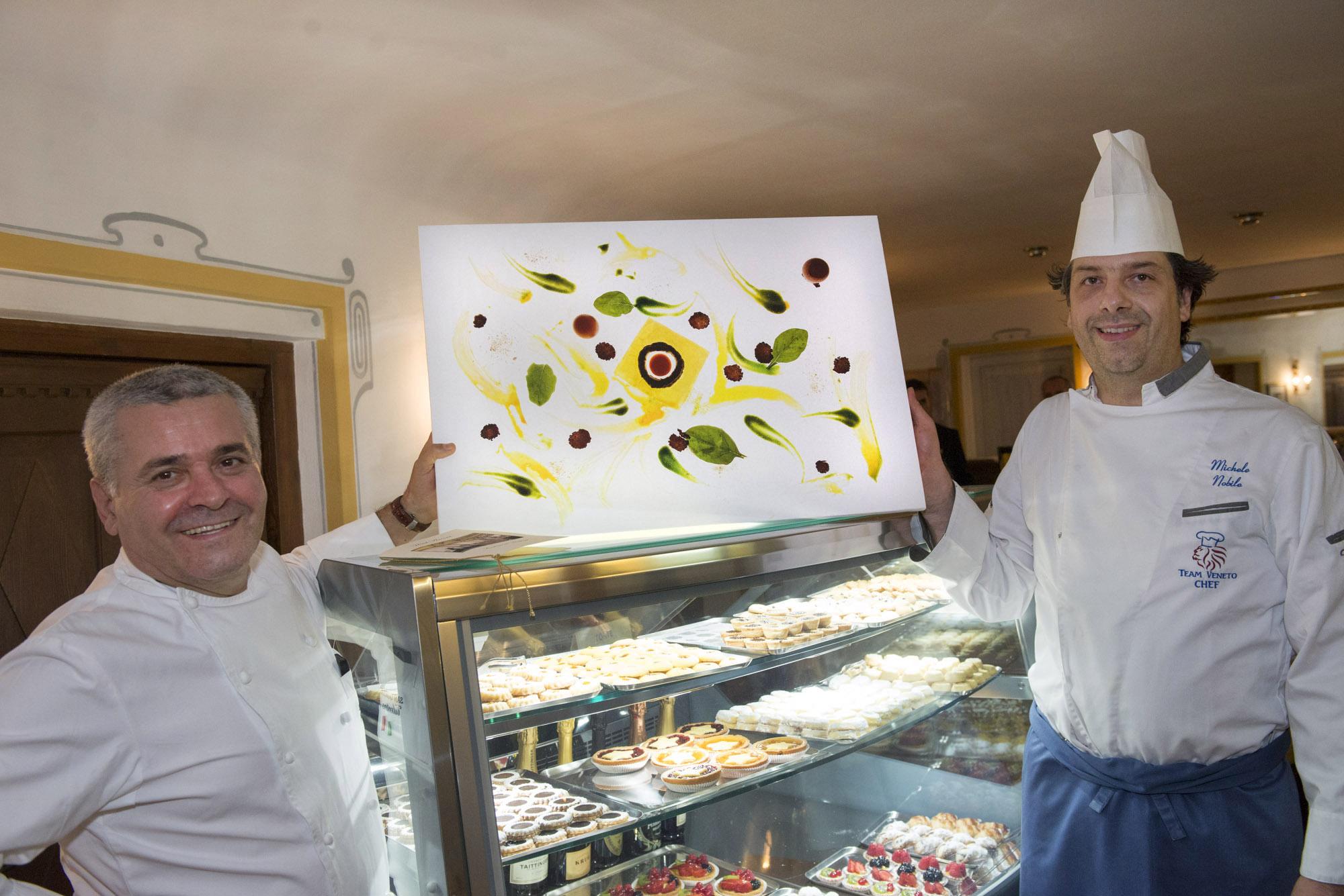"""Gli chef Valentino Marcattilii e Michele Nobile con l'opera  Uovo in raviolo """"San Domenico"""", con parmigiano dolce, burro, nocciola e tartufi di stagione.  (ph Giacomo Pompanin)"""