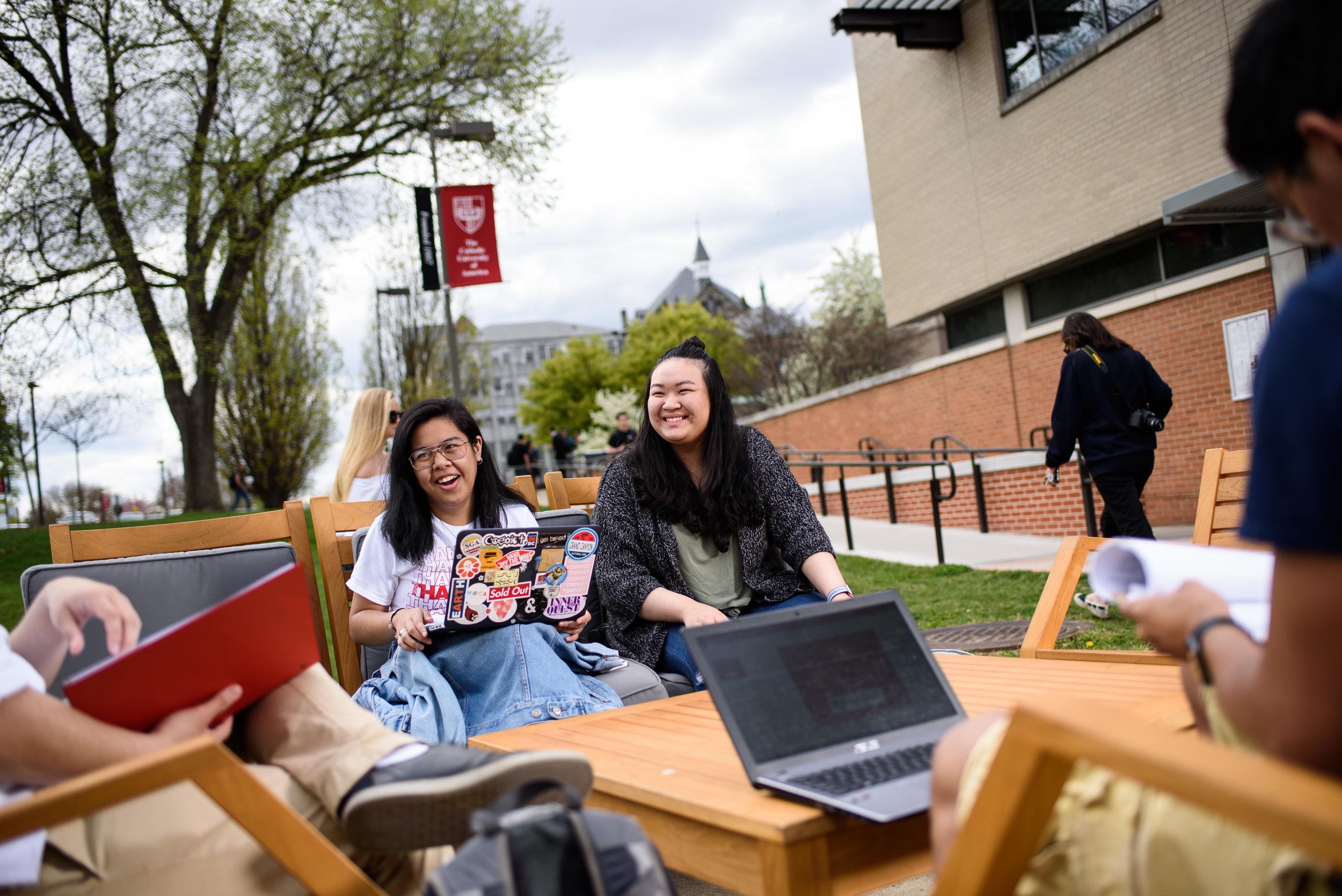 Catholic University students sitting at the benches outside of the Pryz.