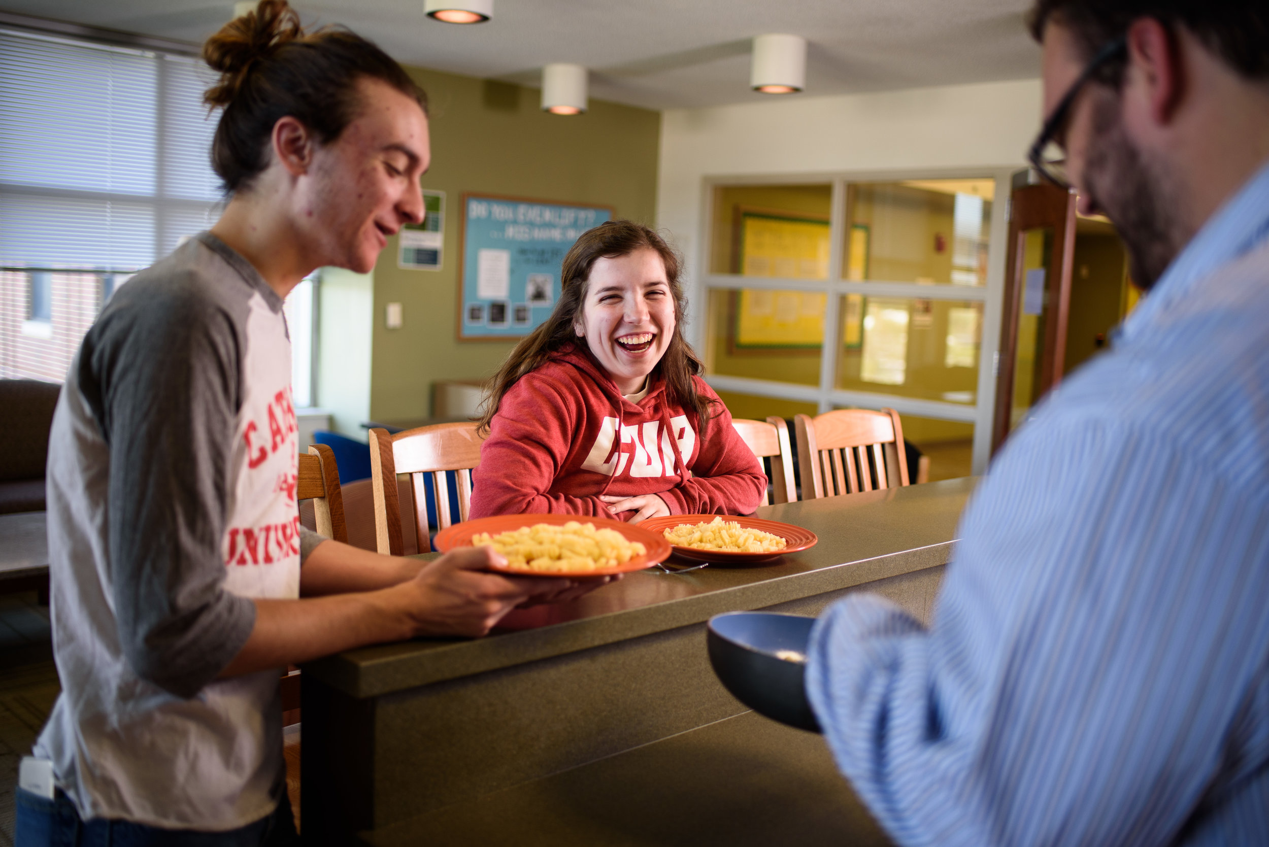 Students cooking and eating in Opus Hall Dorms at Catholic University.