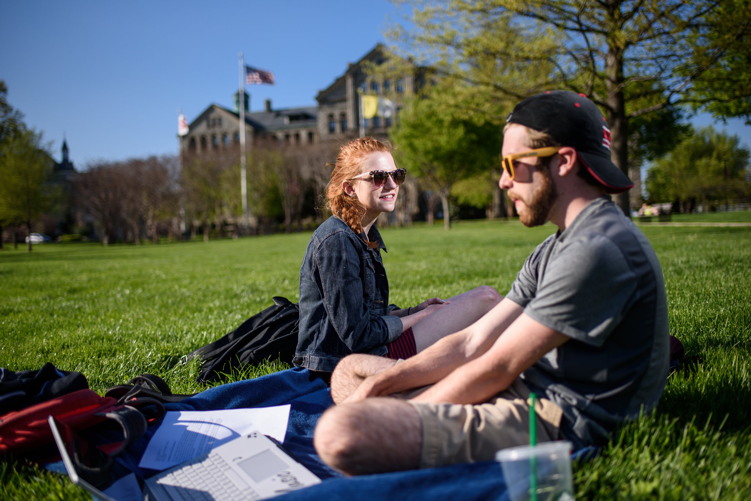 Students sitting in the field in front of McMahon Hall at Catholic University.