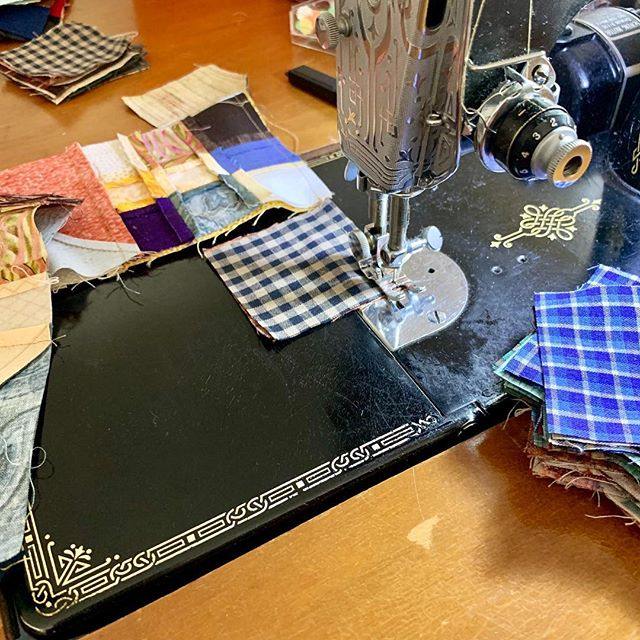 "First time using ""leaders and enders"" — and not by choice. The thread tails kept springing out of my new presser foot, so it was actually faster to sew 2x as many pieces together. (Image: black Singer Featherweight with a stack of 2.5-inch squares and three pieces still attached under the presser foot.) #Featherweight #quilting #leadersandenders #bonniehunter"