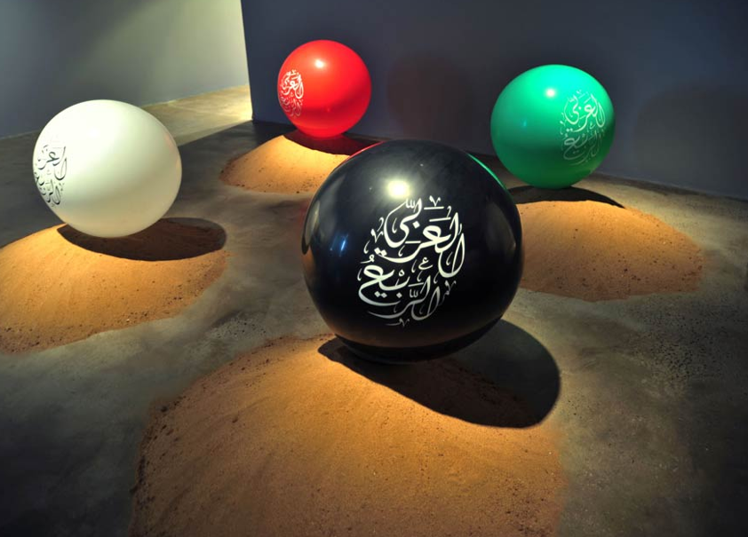 Across the road, Ayyam Gallery struck a more serious note, presenting some of the most powerful pieces including this installation, entitledArab Spring, by artist Faisal Samra, whose solo exhibition 39 at Ayyam Gallery runs until 10 January 2015. An eery piece, consisting of 22 grave-like mounds of sand, one for each country in the Arab world, with large balloons inscribed with the words 'Arab Spring' in Arabic calligraphy as headstones. An eery piece with a complex, reflexively critical message, occasionally made even eerier by unattended children playing with the sand.