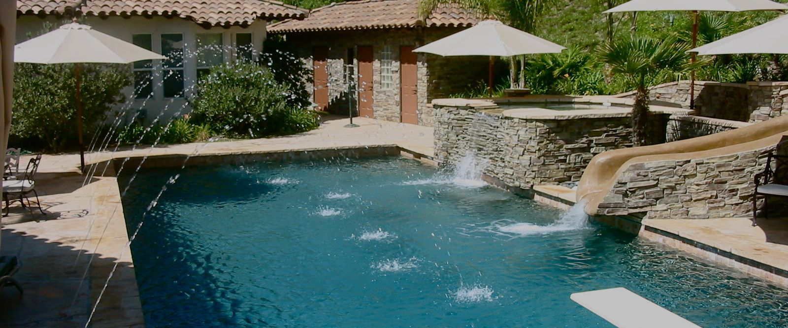 Pool with spa overflow, slide and water features.jpg