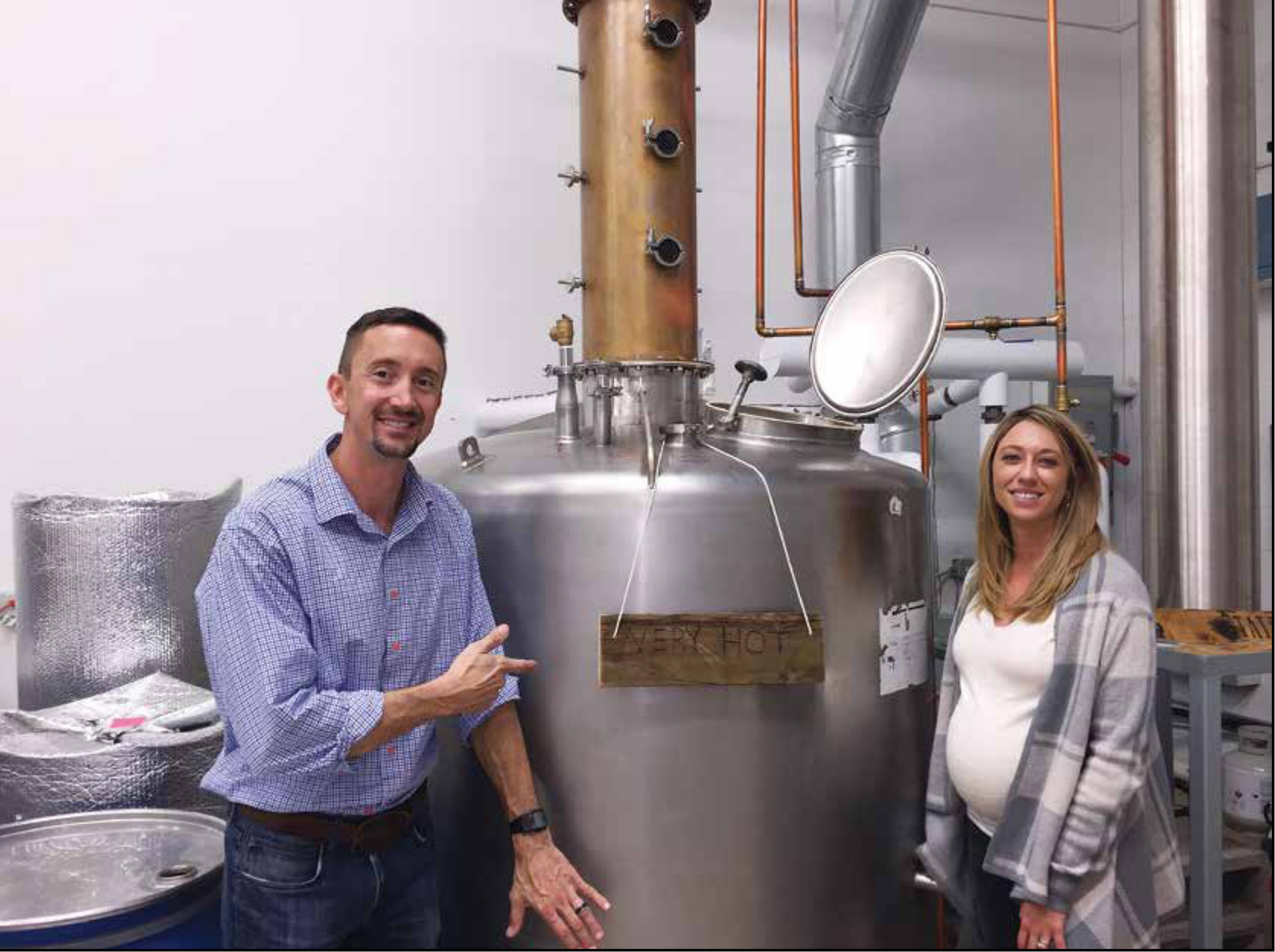 Sean Smiley and his wife Jessie show off a 250-gallon still that he constructed from a milk pasteurizer. Jessie went into labor a few hours after this picture was taken and their son Jordan was born in the wee hours of the next day. Photo © Bill Owens