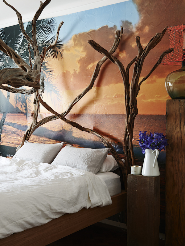 Main bedroom. Inbed linen sheets, coastal tea tree four post bed frame by Dion Antony Artisan, glass lamp with neon shade also made by Dion.Sunset wall paper back drop. Photo – Eve Wilson. Production – Lucy Feagins/The Design Files.
