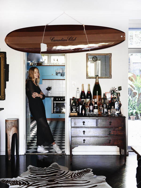 Bar/ kitchen. Flame sculptured stool (to left) by Dion Antony Artisan, vintage dresser, canadian club wood surf board. Anna wears vintage Ksubi dress, converse shoes , Mania Mania rings. Photo – Eve Wilson. Production – Lucy Feagins/The Design Files.
