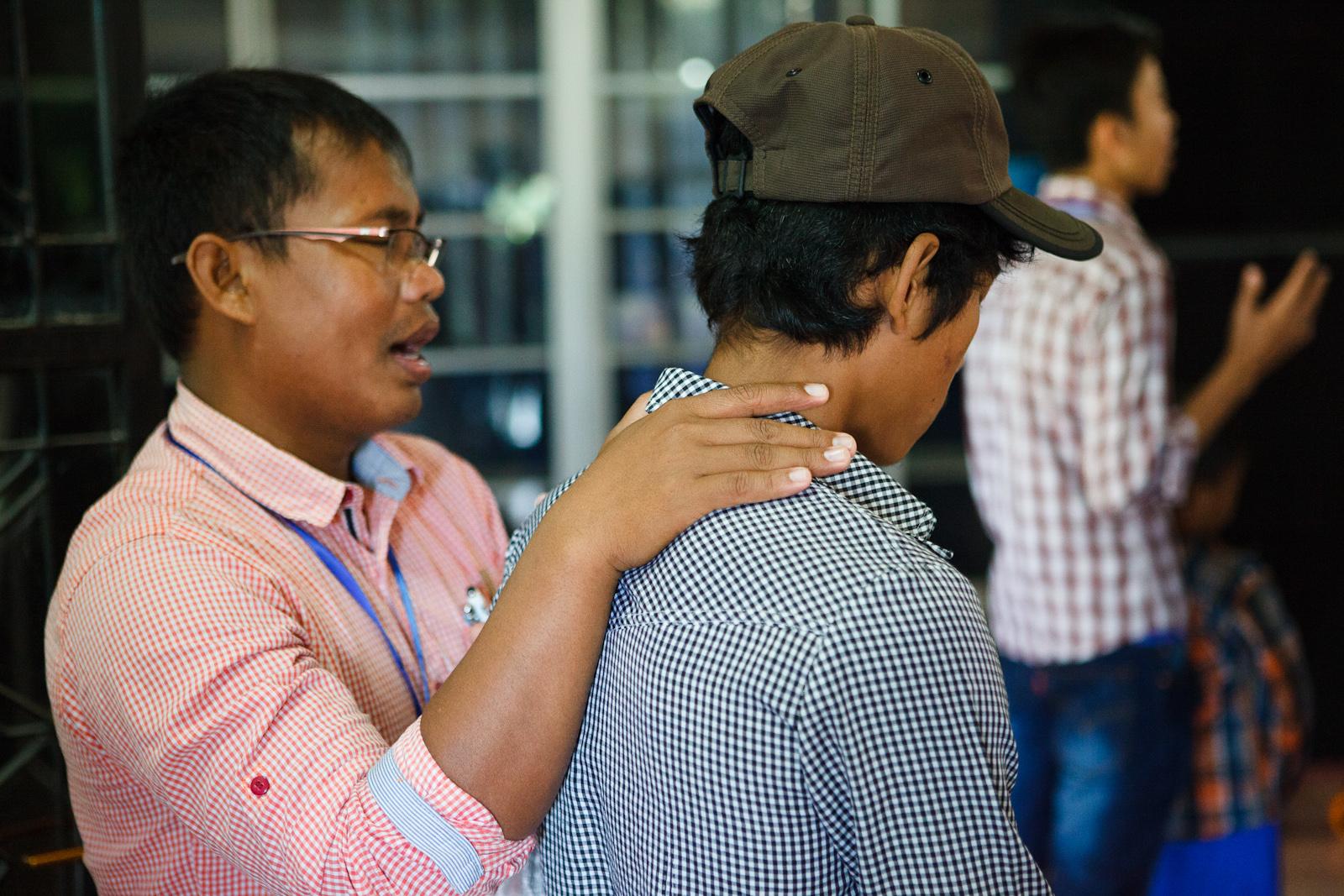 Narith's Alongsider mentor, Kimyan, praying for him at camp