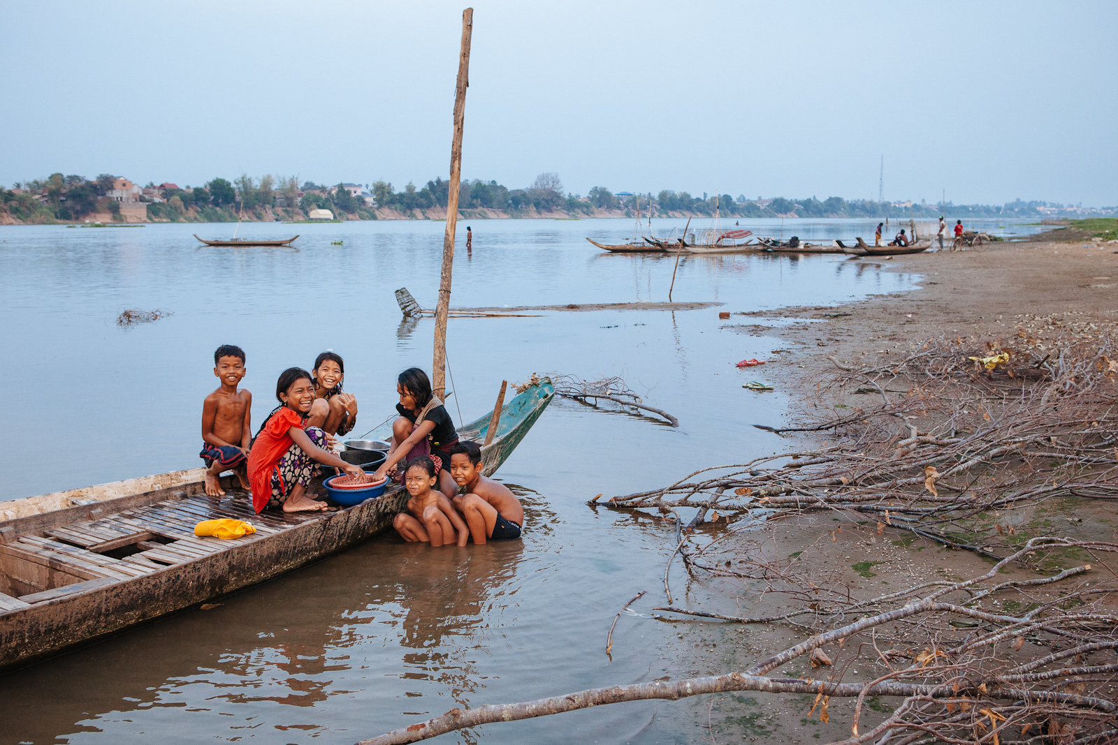 Community children in a riverside village play and do chores at dusk.