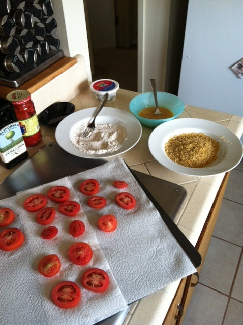 Slice tomatoes and put flour and bread crumb mixtures in bowls near stove top.