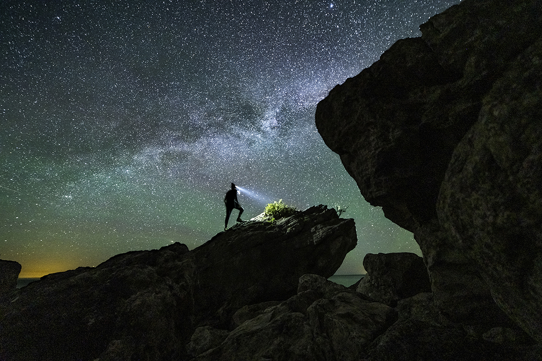 Taking in the starry views from atop a rock