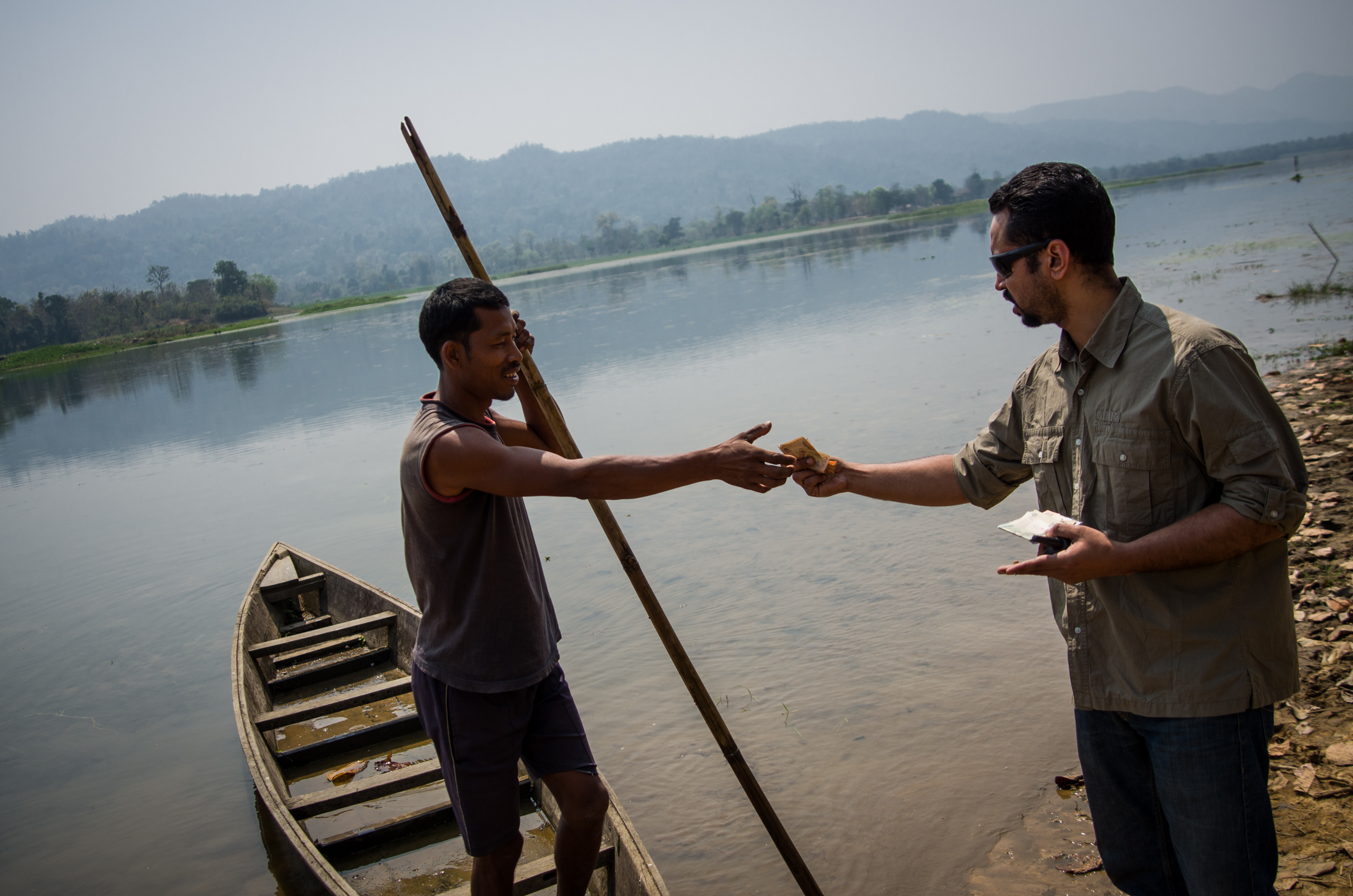 Neel paying local for a boat ride while scouting new land in Assam.