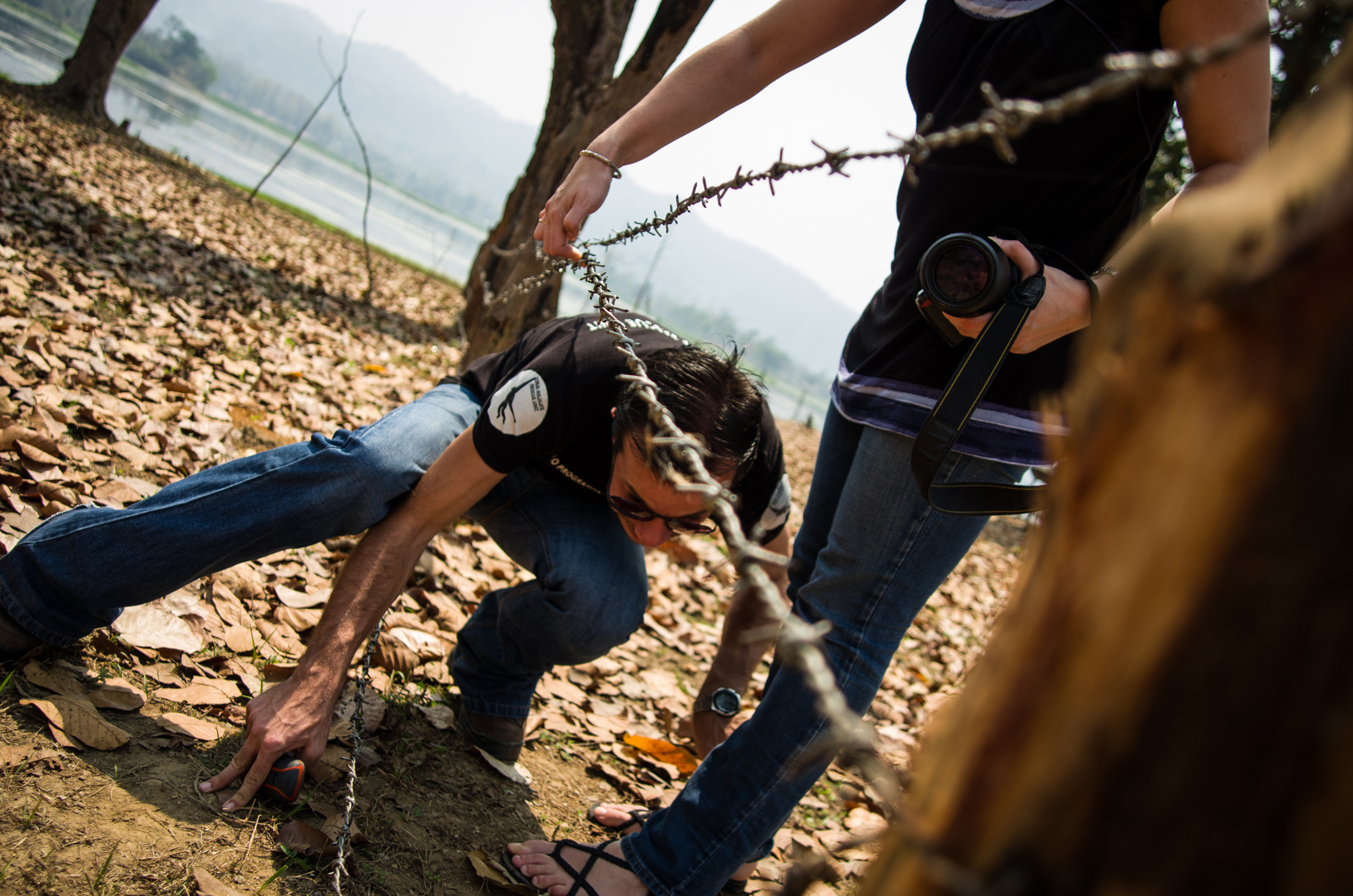 Mathilde lifts a barbwire fence for Florian while scouting new land in Assam.