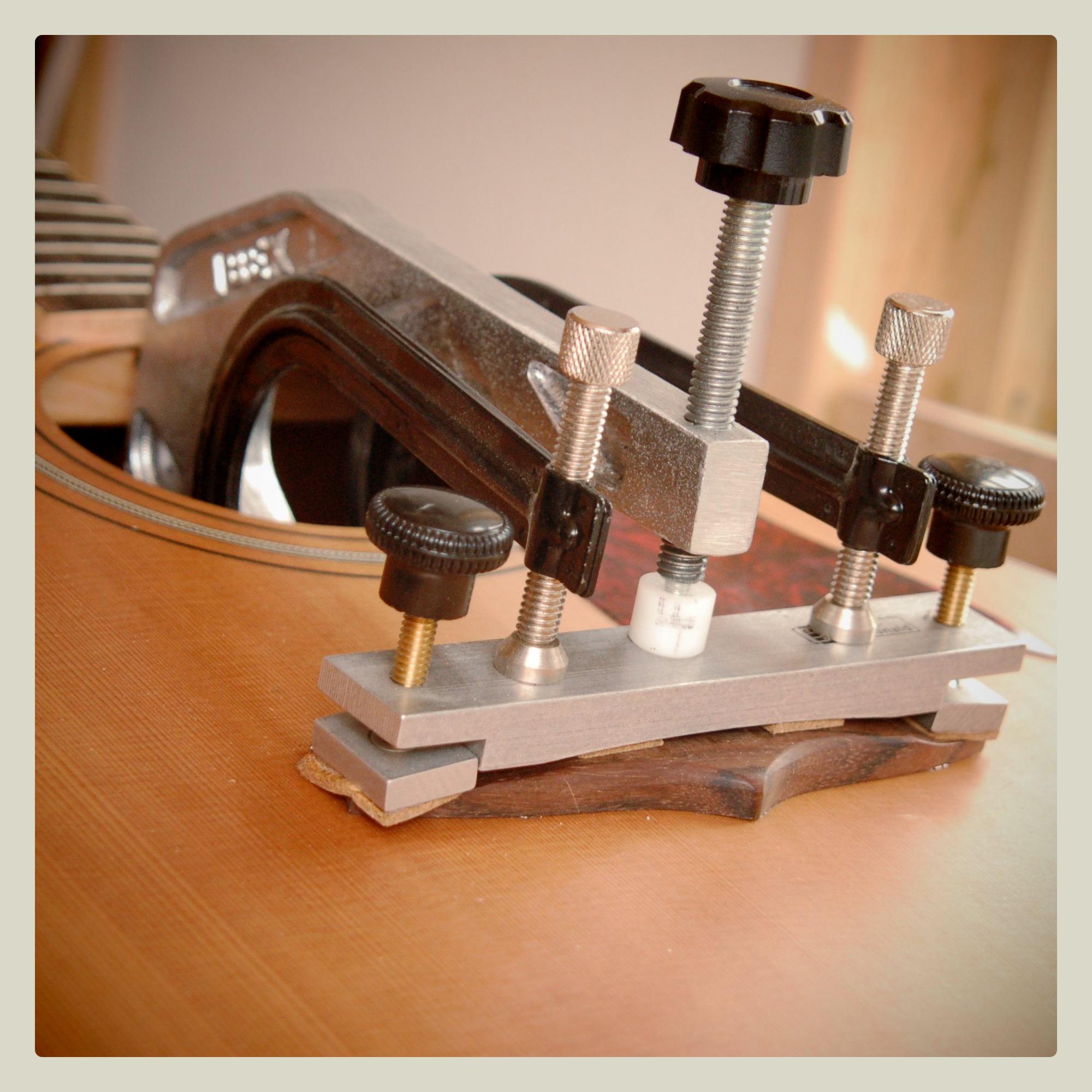 Clamping a repaired lifting acoustic guitar bridge