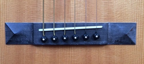 String compensation. Saddle on acoustic guitar angles to allow bigger strings more compensation
