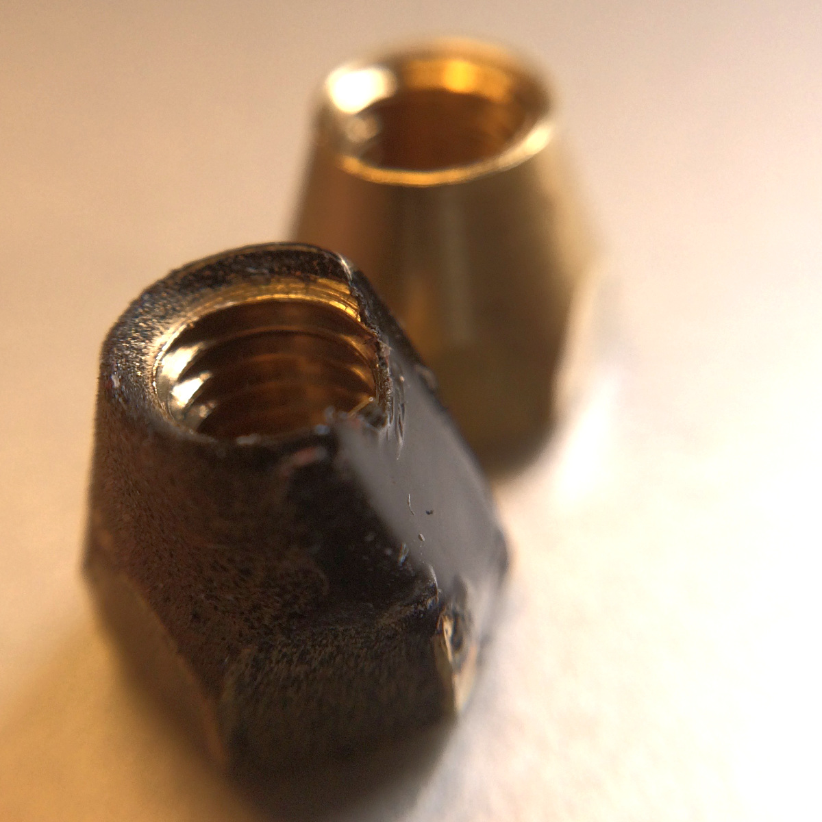 Comparison showing ground portion on truss rod nut (front) and normal nut (back)
