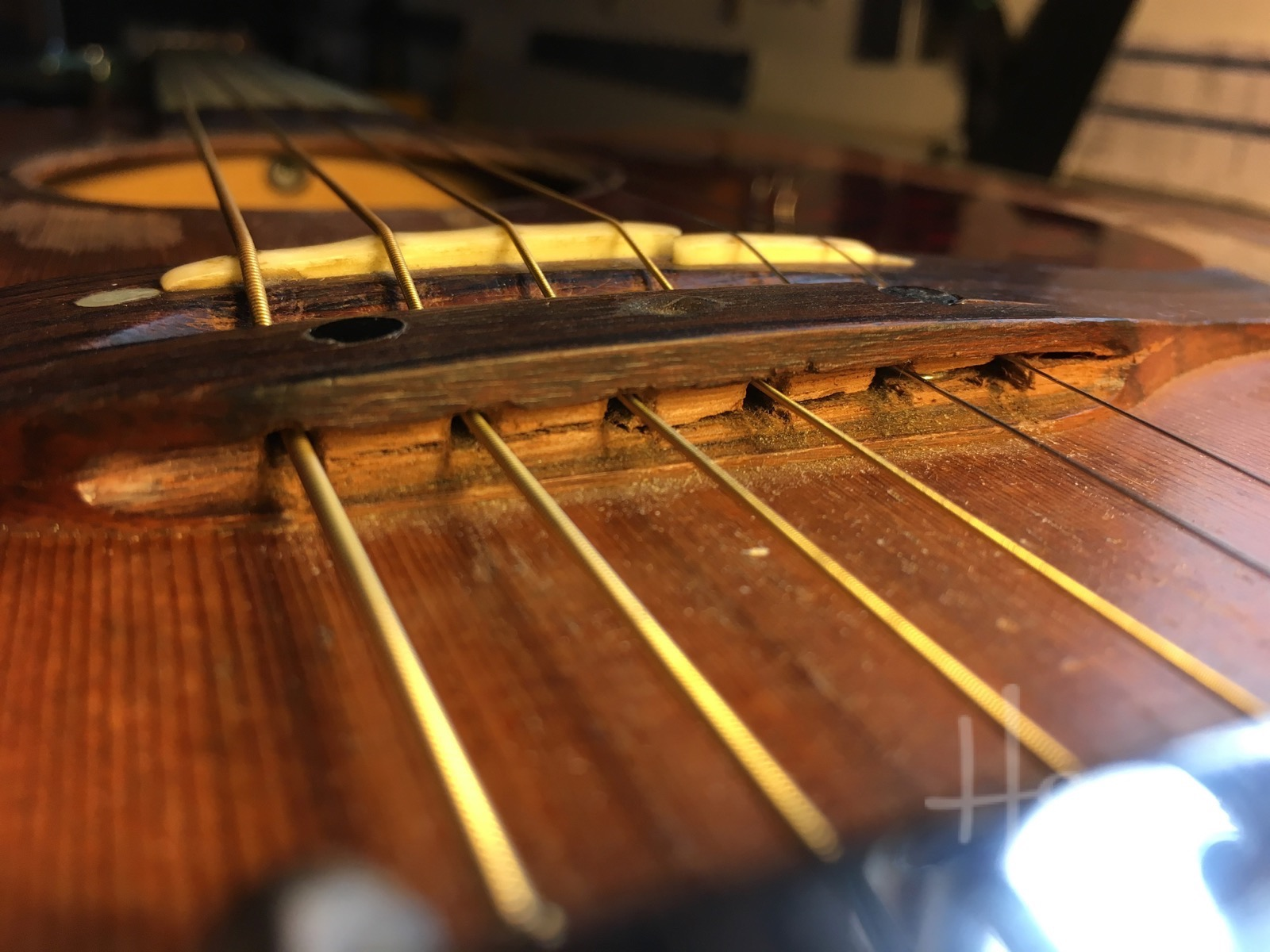 Here's the reason for that weird repair. This Takamine has a seriously cracked bridge
