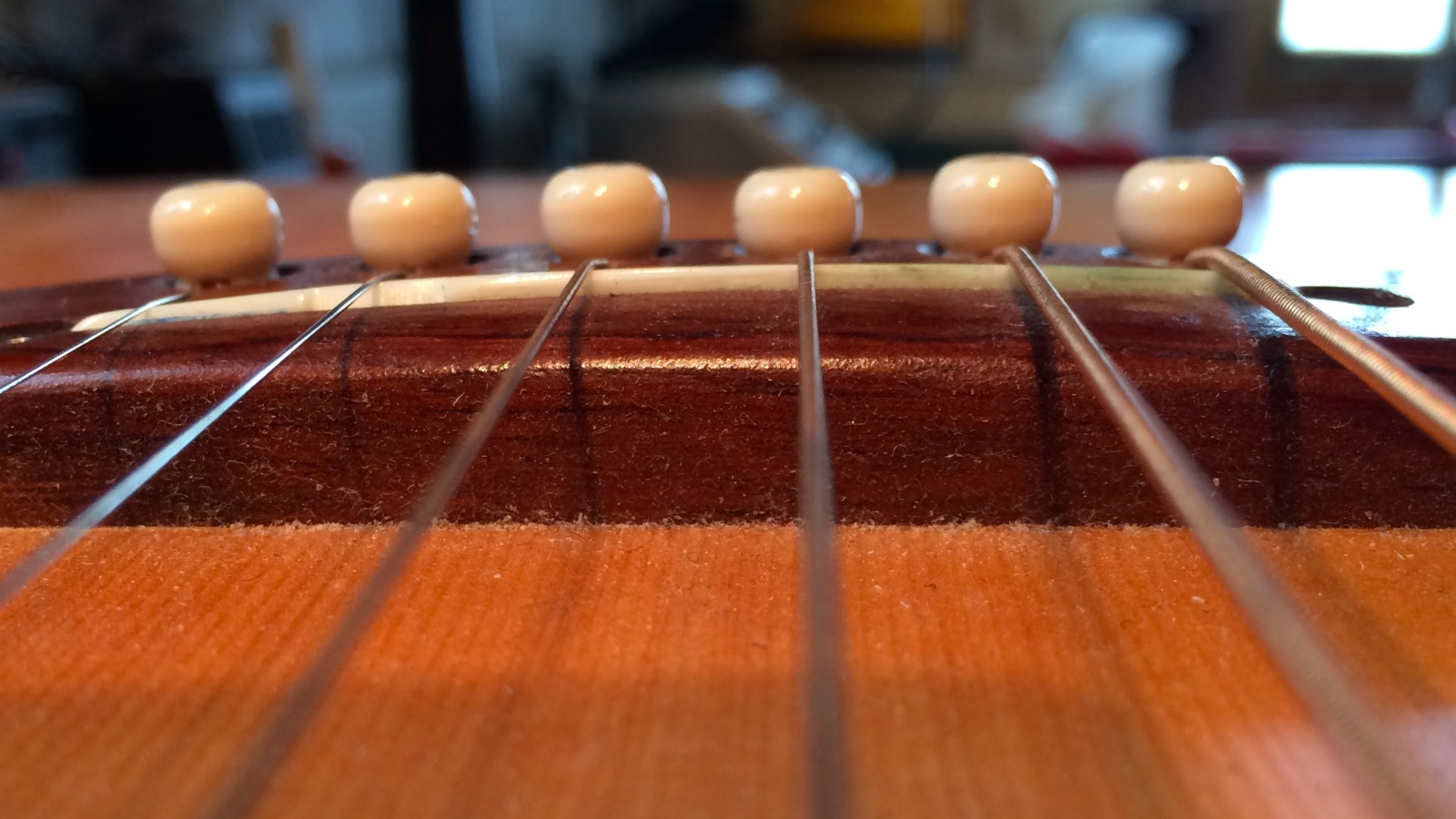 This acoustic guitar saddle is too low. And the action's still too high.