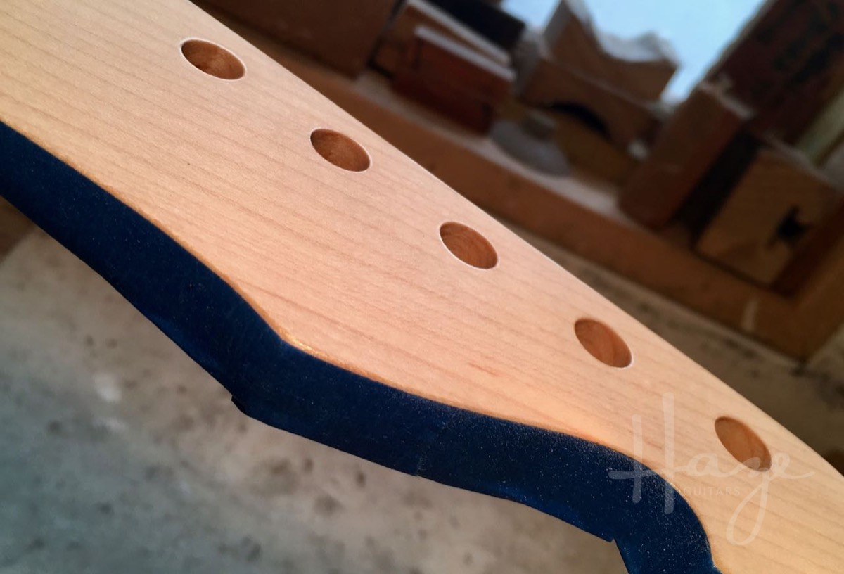 To prep headstock for logo application, lay down a couple of coats and flatten