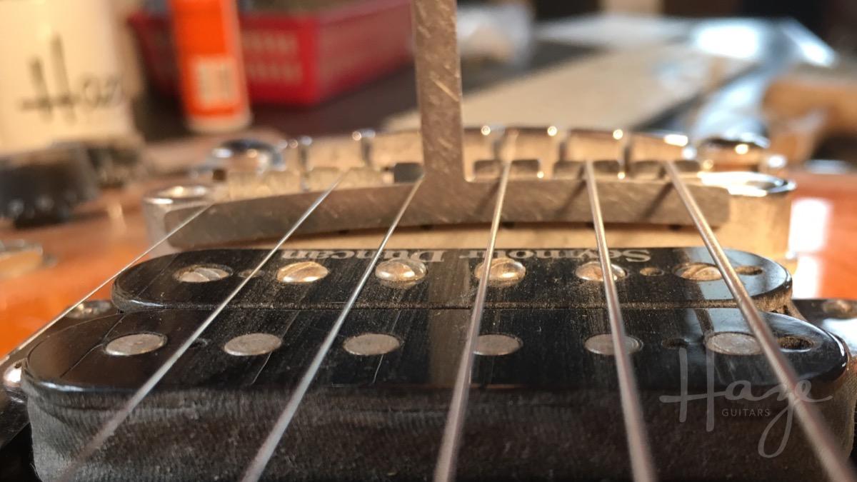 Setting string action with under-saddle radius gauge.