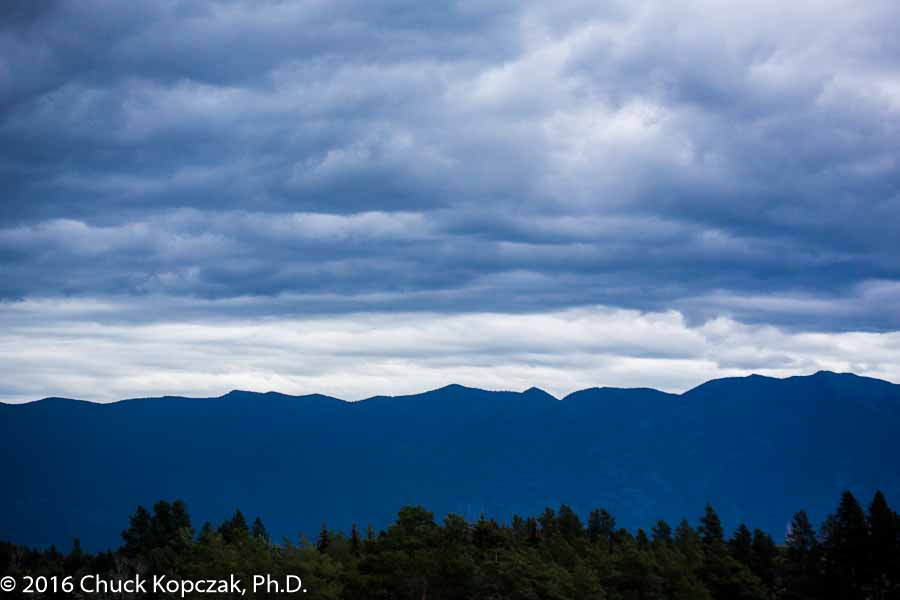 The Swan range in northwestern Montana is silhouetted in purple tones beneath threatening clouds.