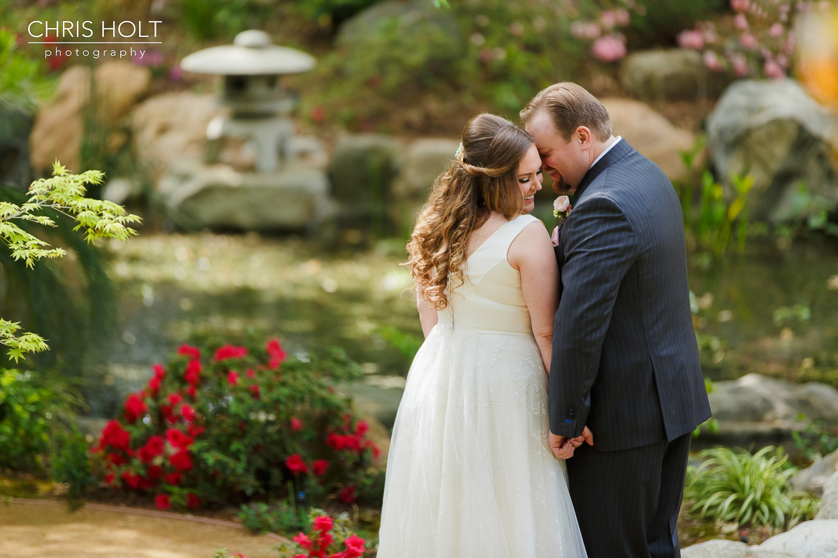 Bride and Groom romantics at Storrier-Stearns Japanese Garden in front of koi pond