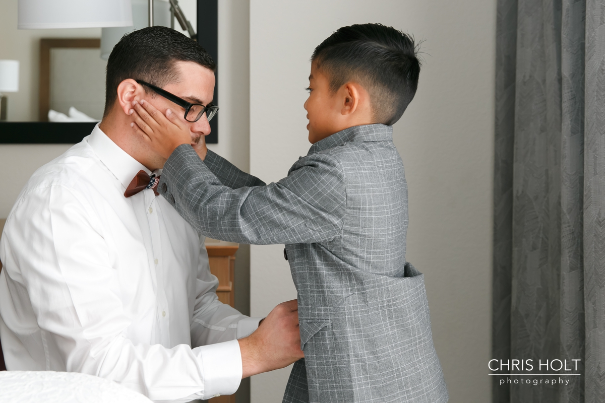 son helping his dad the groom smile