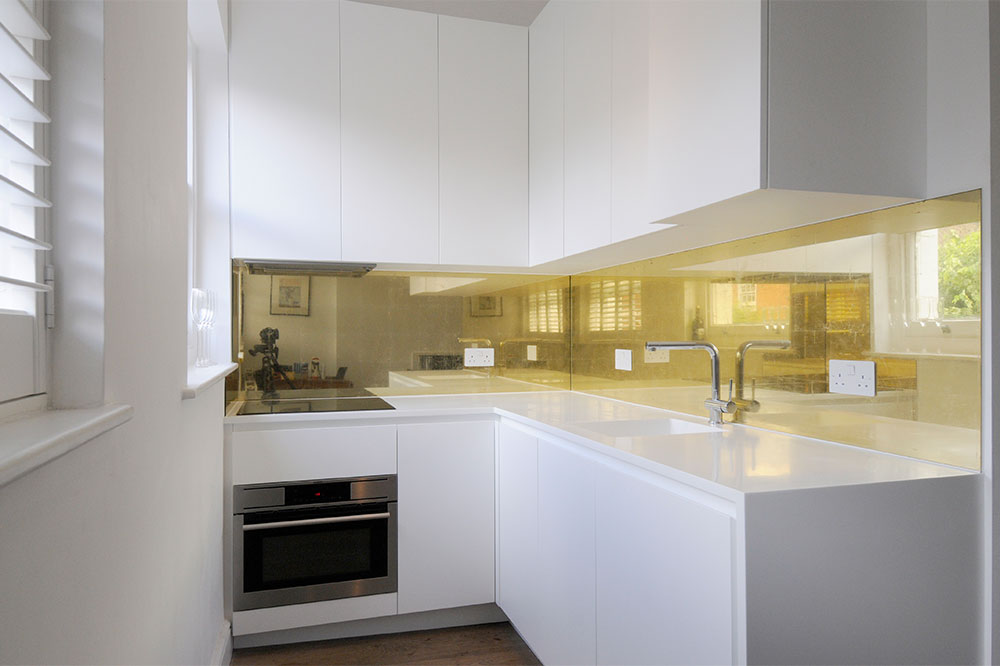22 carat gold leaf was chosen for this kitchen splashback to bring balance and warmth to this all white minimalist kitchen.  Collaboration with designer Tom Bussmann.