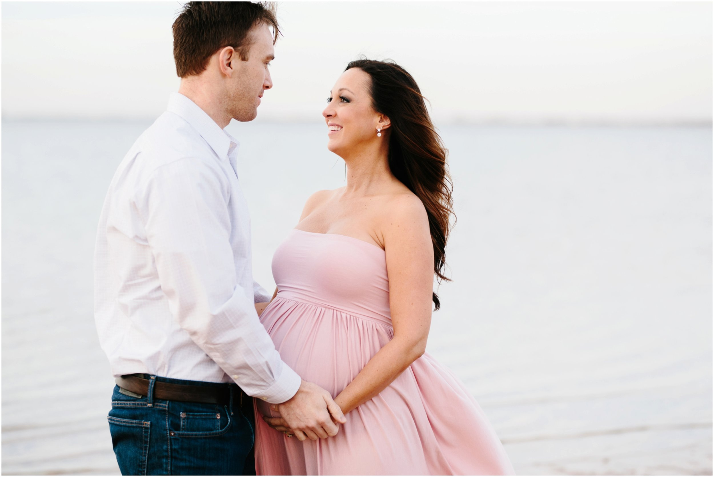 expecting parents holding hands on beach in maternity photos edmond ok