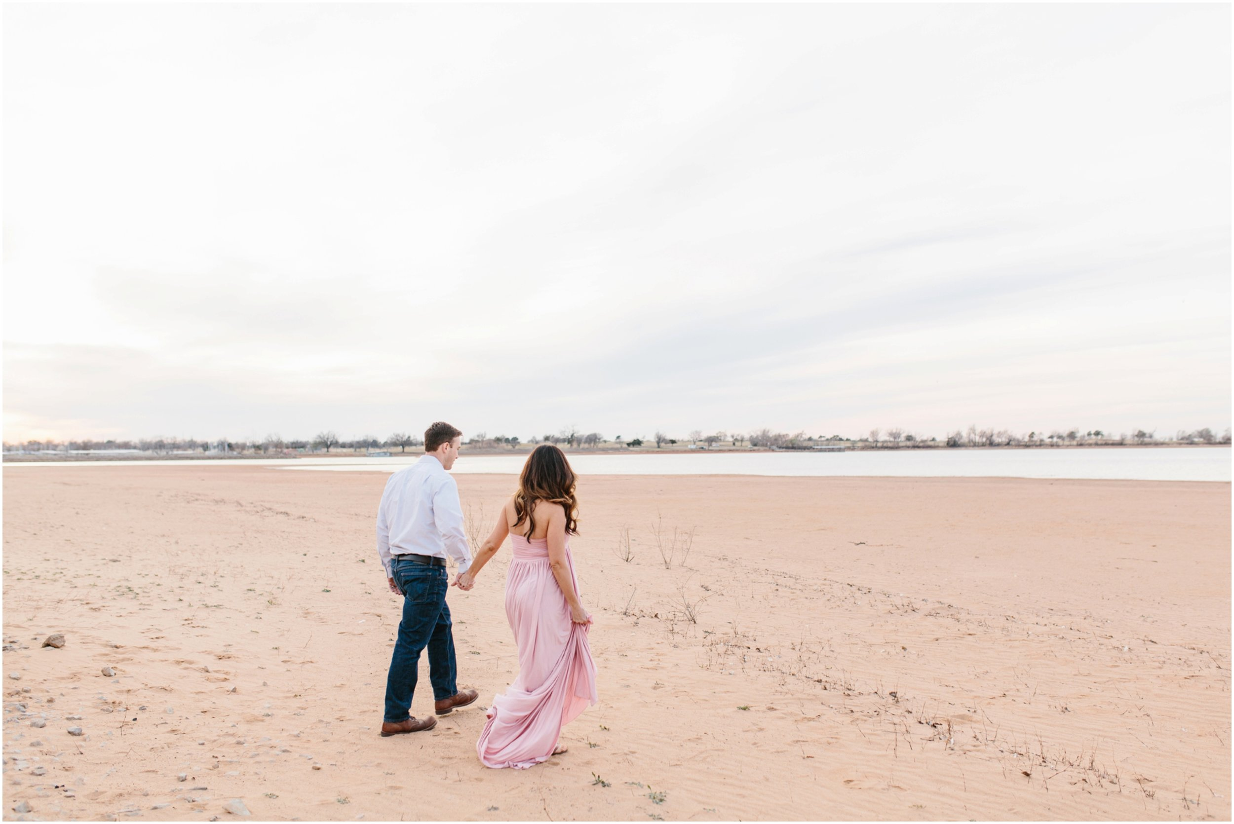 couple walking on beach in midwest open blue sky light pink maternity dress